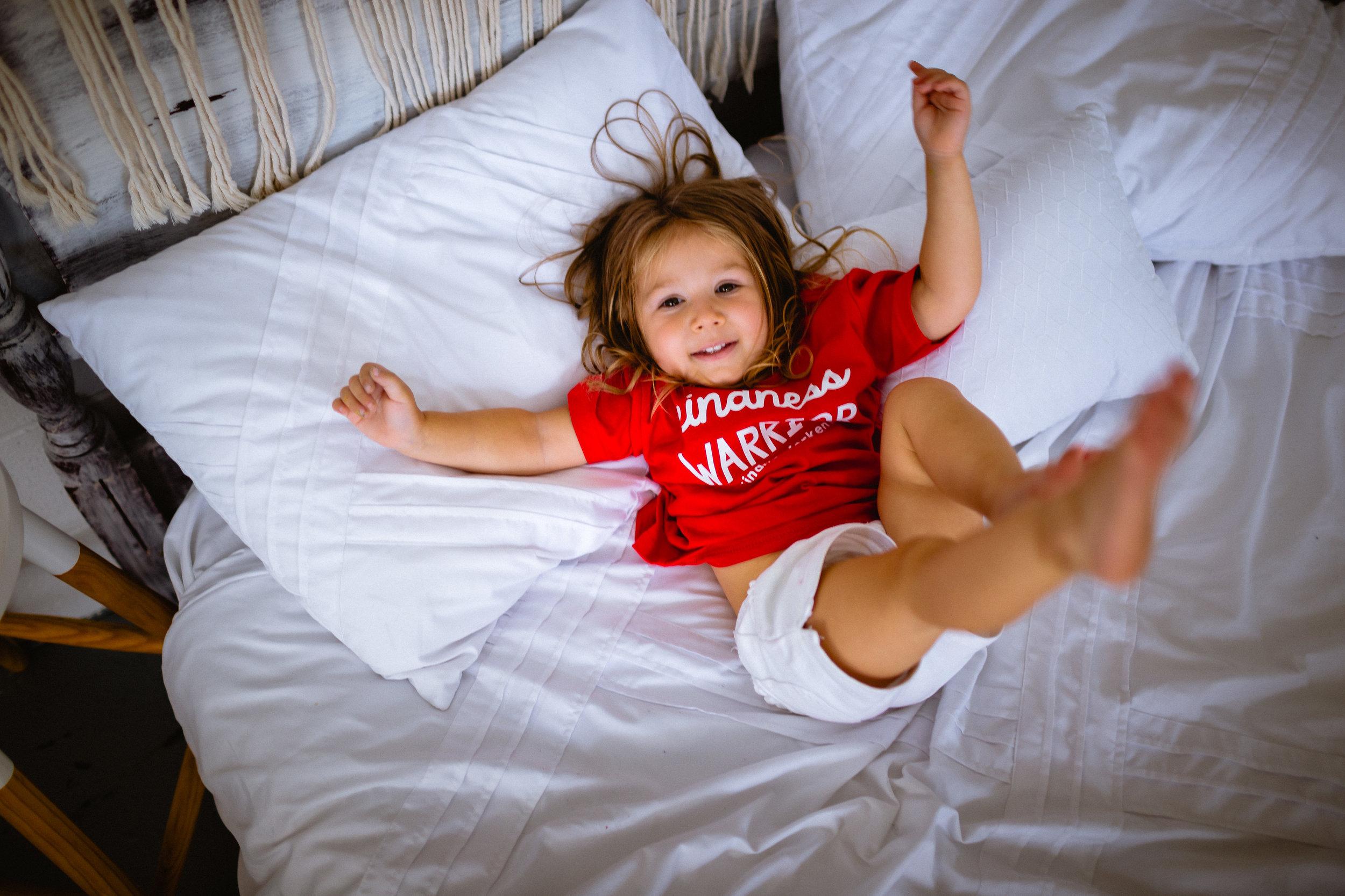 child on bed posing studio photographer