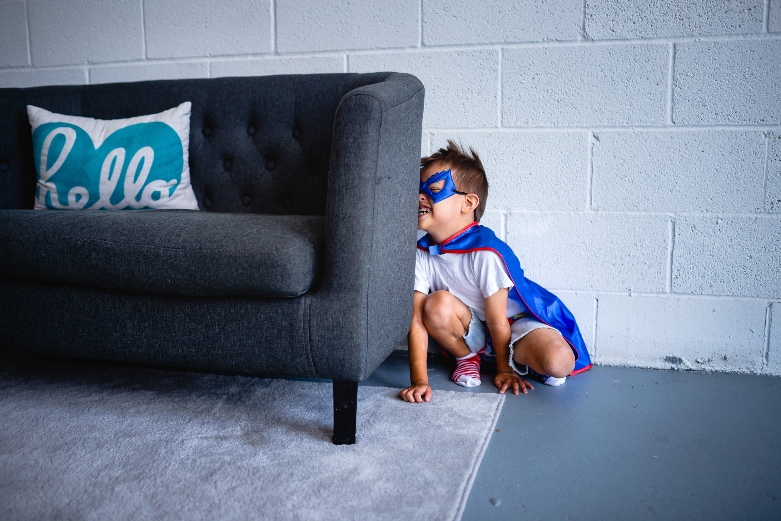 boy playing hide and seek with super hero cape on fort leonard wood photographer