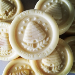 """Various versions of """"save the bee"""" are found everywhere. In this photo, the words """"save the honey bee"""" appear on one of my beeswax lotion bars."""