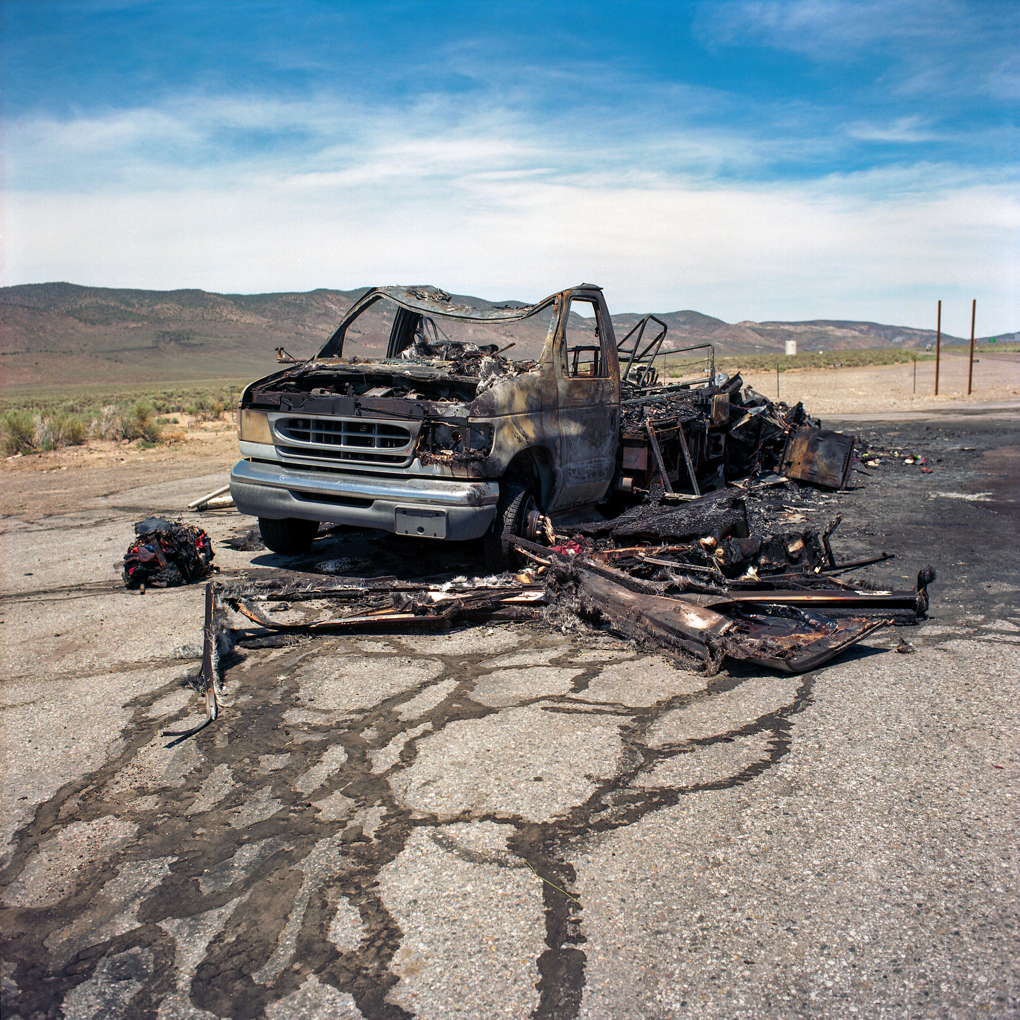 A burnt out van on the highway in Nevada.