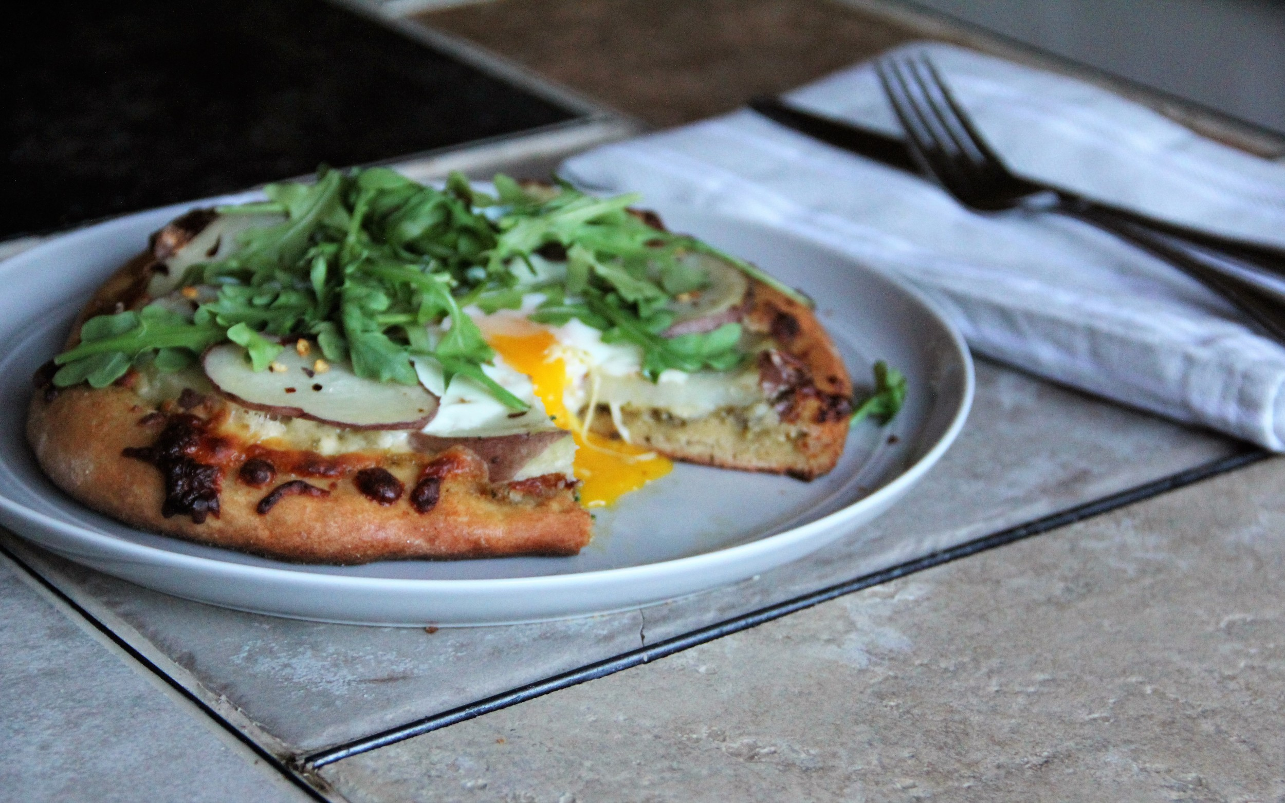 Sunny-side-up eggs, potato, arugula, cheese and pesto pizza! Perfect for Brunch or Dinner.