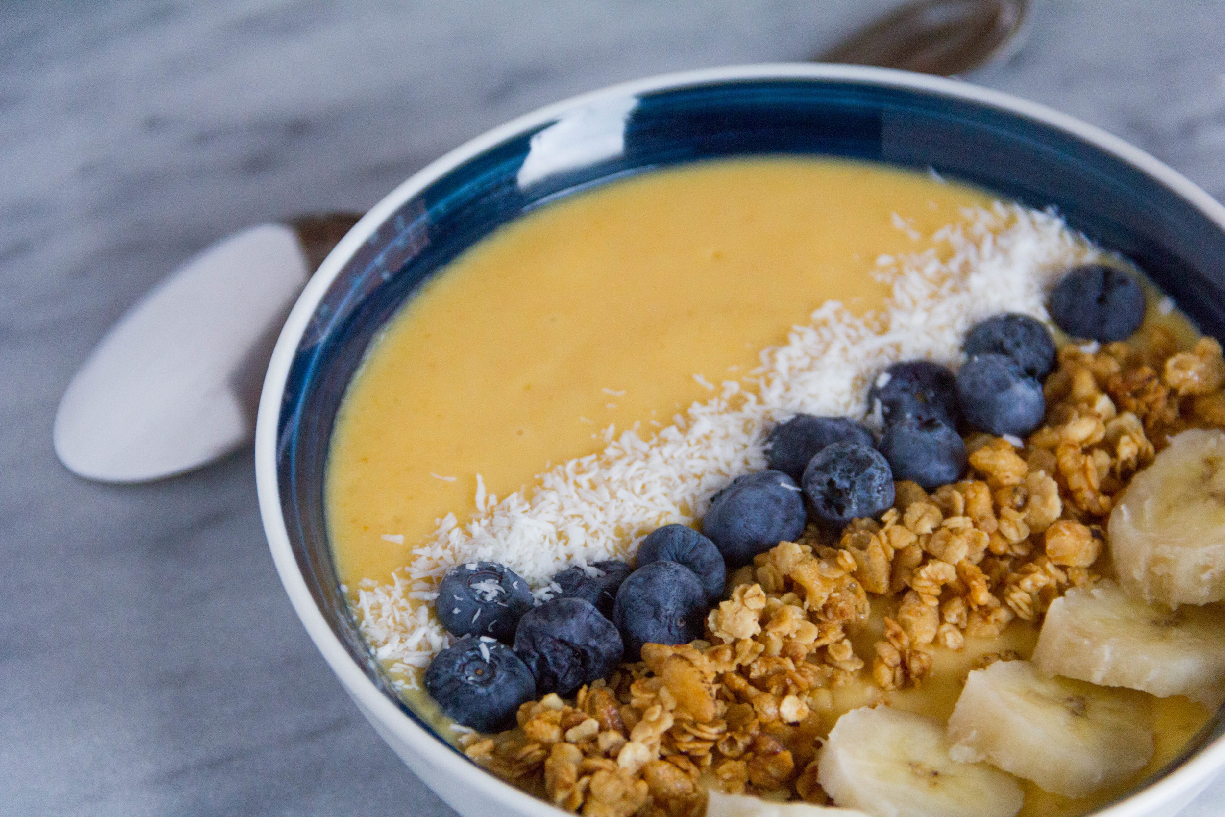 Pumpkin Mango Smoothie Bowl... topped with very ripe banana, homemade gluten free granola, fresh blueberries, and unsweetened coconut flakes!