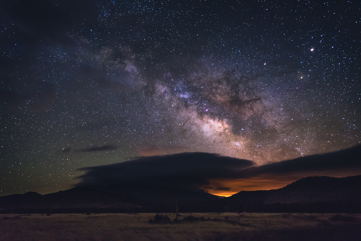 The Milky Way over Humphrey's Peak's summit engulfed in clouds, the orange sky glow is from Flagstaff, about 30 miles south