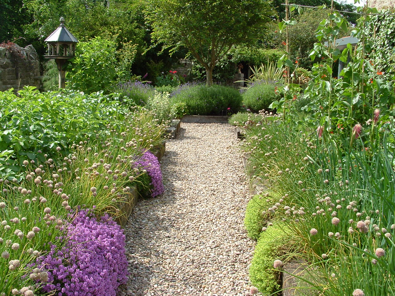 Traditional herb garden with a gravel path edged by timber board raised beds.