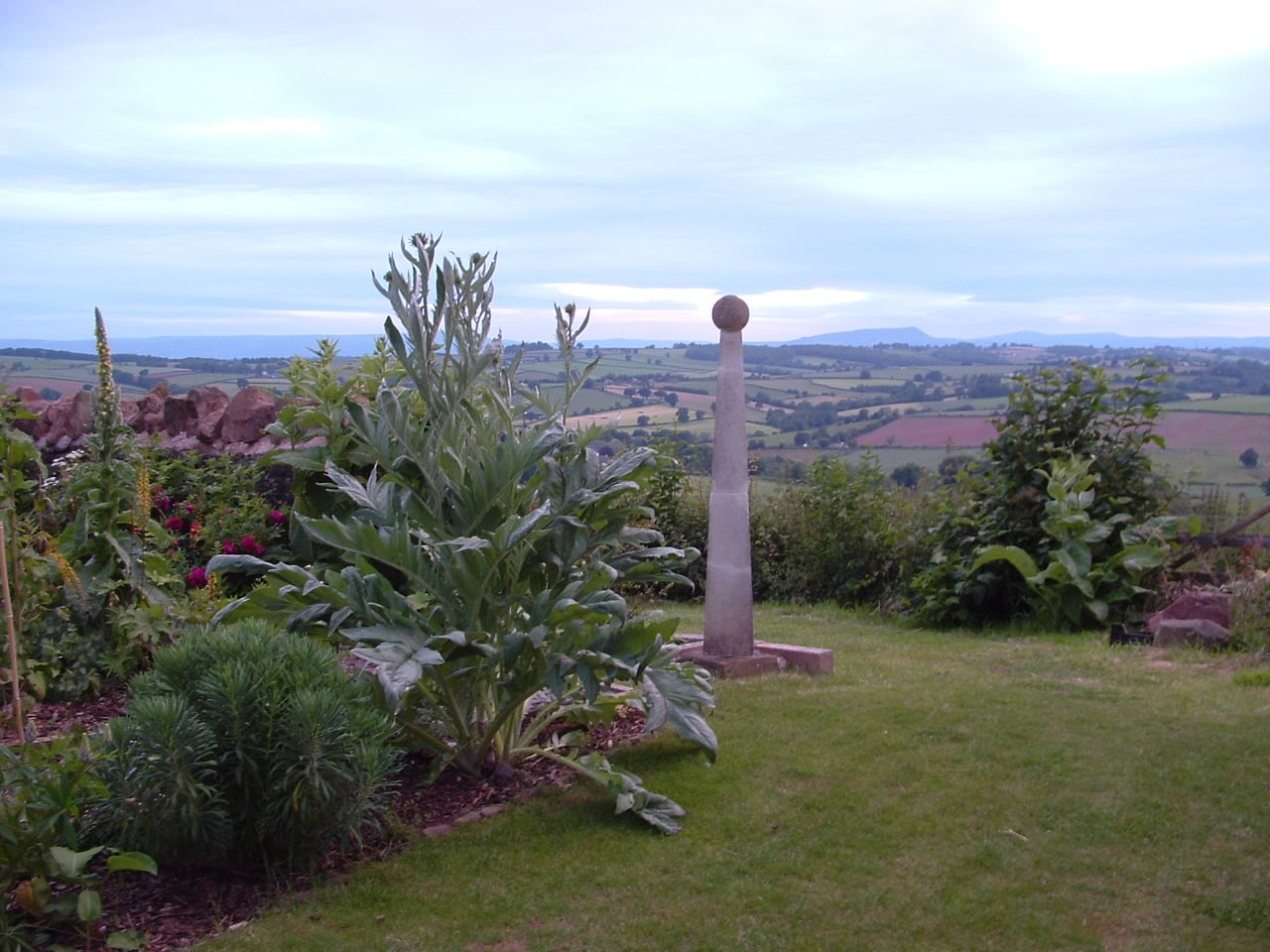 In a hilltop garden with a spectacular view, a stone obelisk draws the eye into the distance.