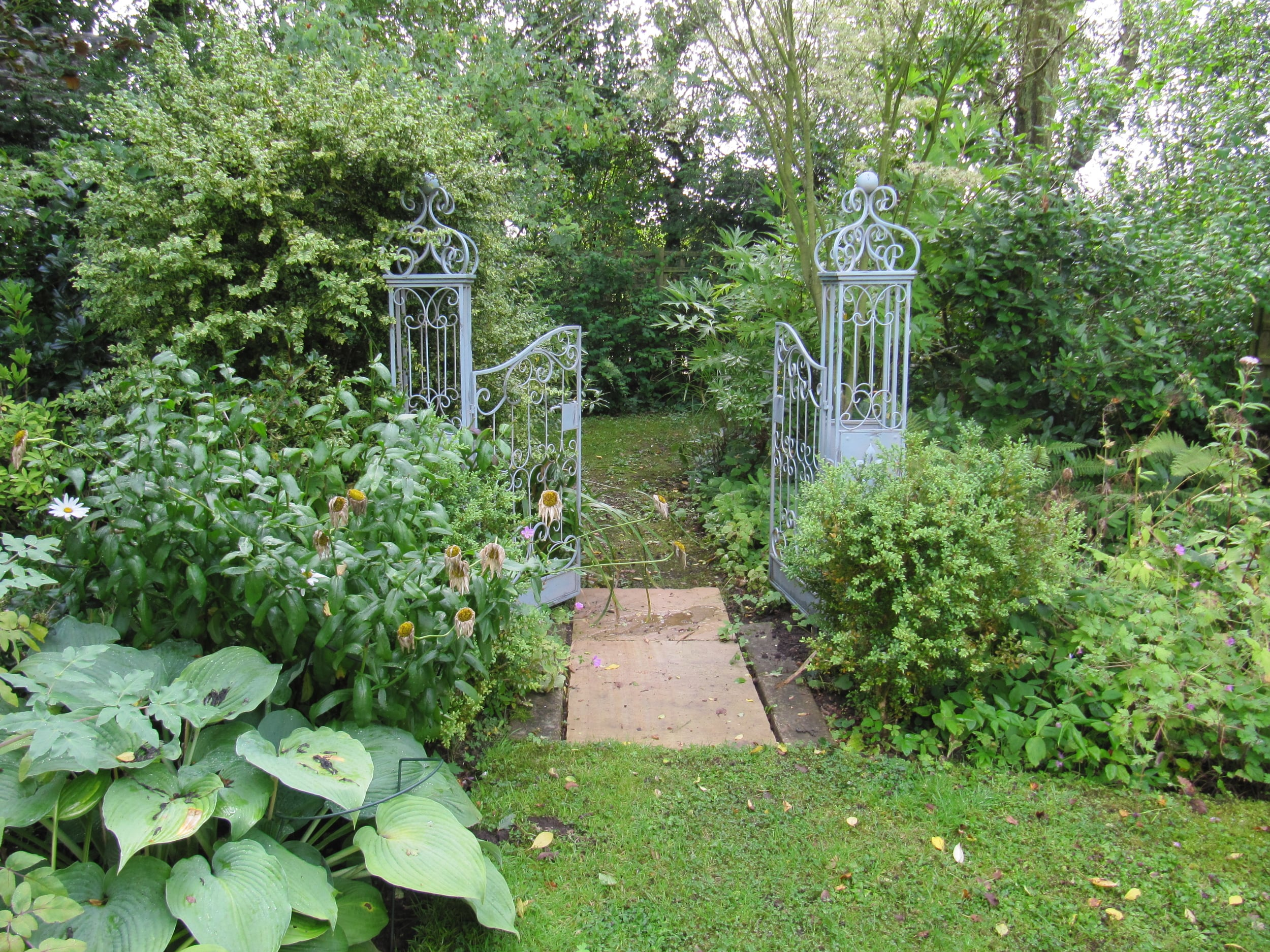 Painted wrought iron gates form a quirky entrance inviting further exploration of this Herefordshire garden.