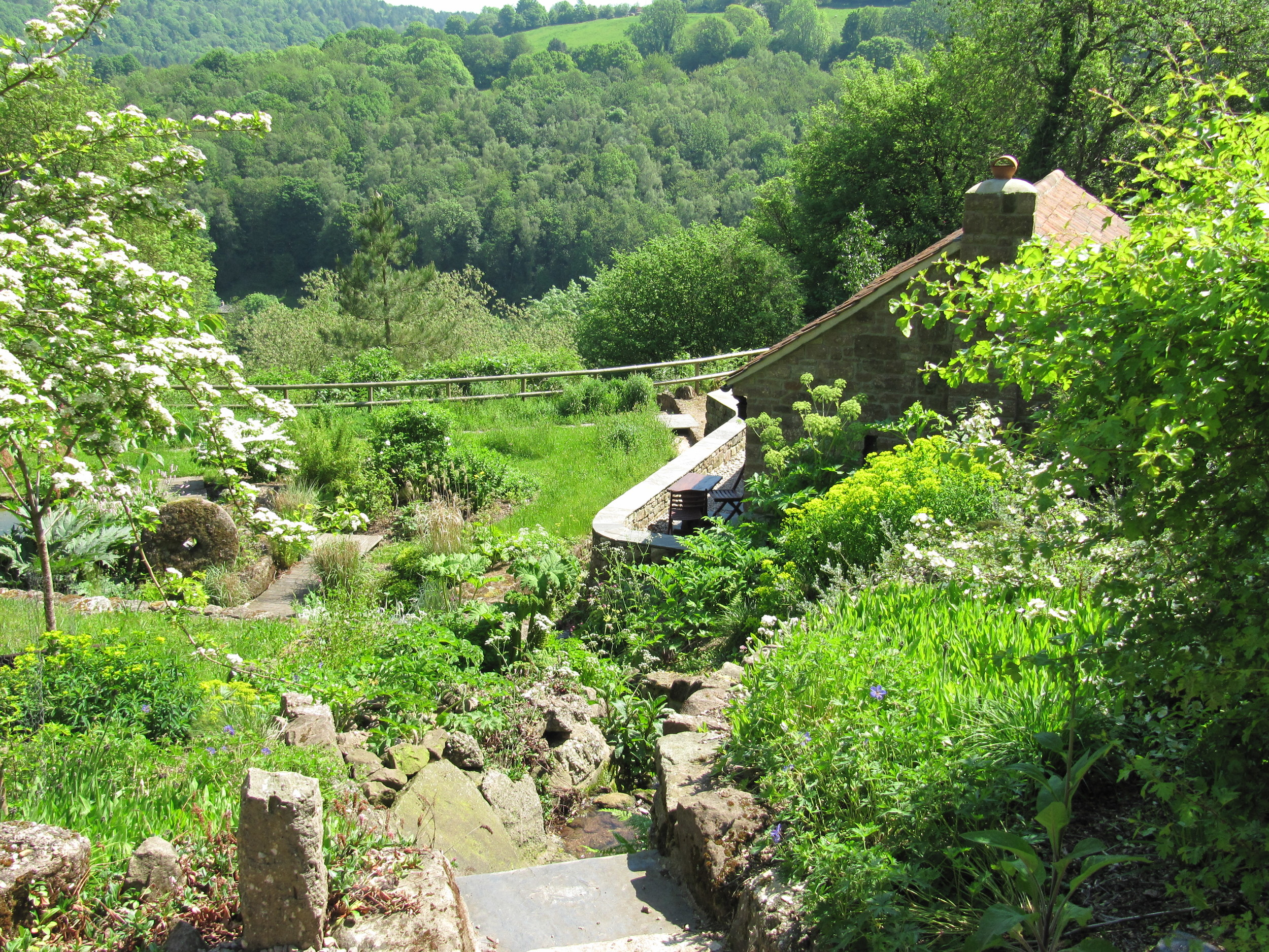 A path through a rock strewn hillside funnels the view over the garden and Wye Valley to a spectacular view of the Forest of Dean