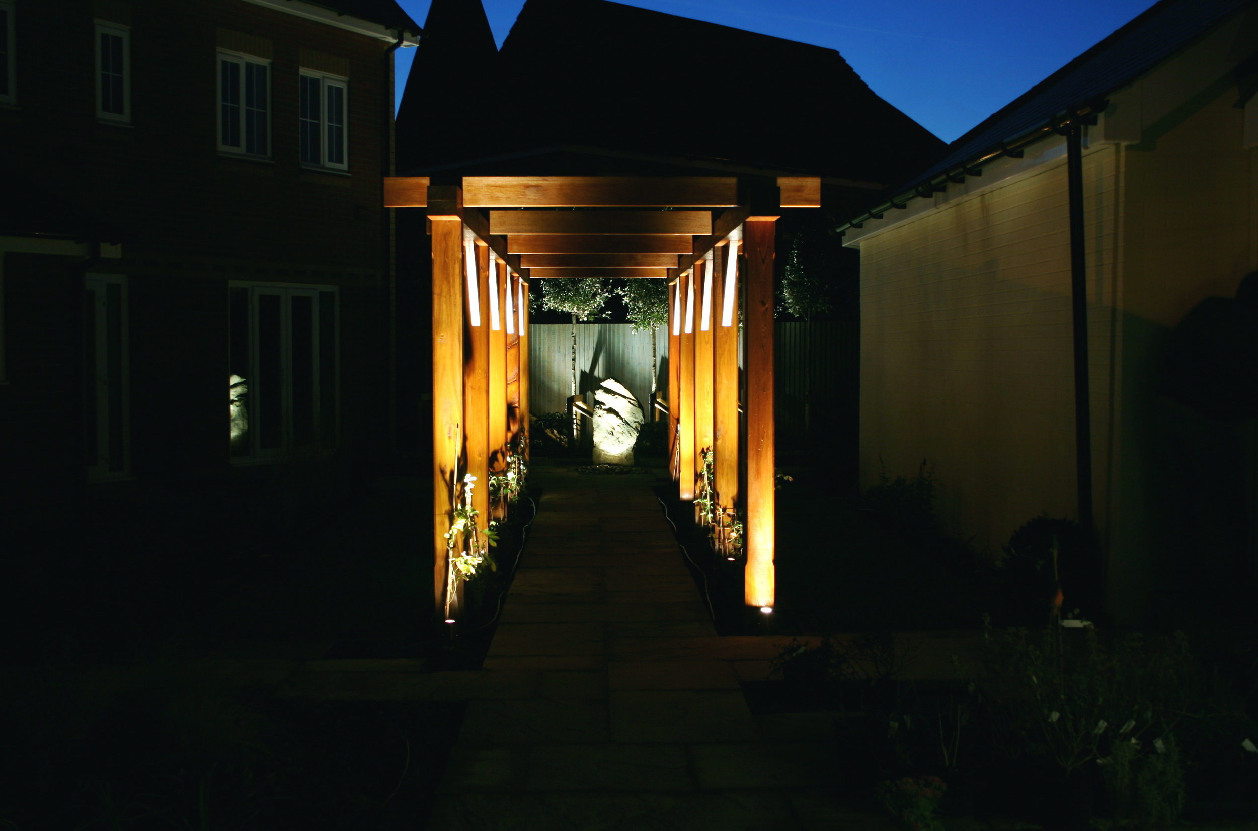 Dramatic lighting adds a huge amount of interest to the night garden, when covered in foliage this pergola with act as a screen to sit beneath.