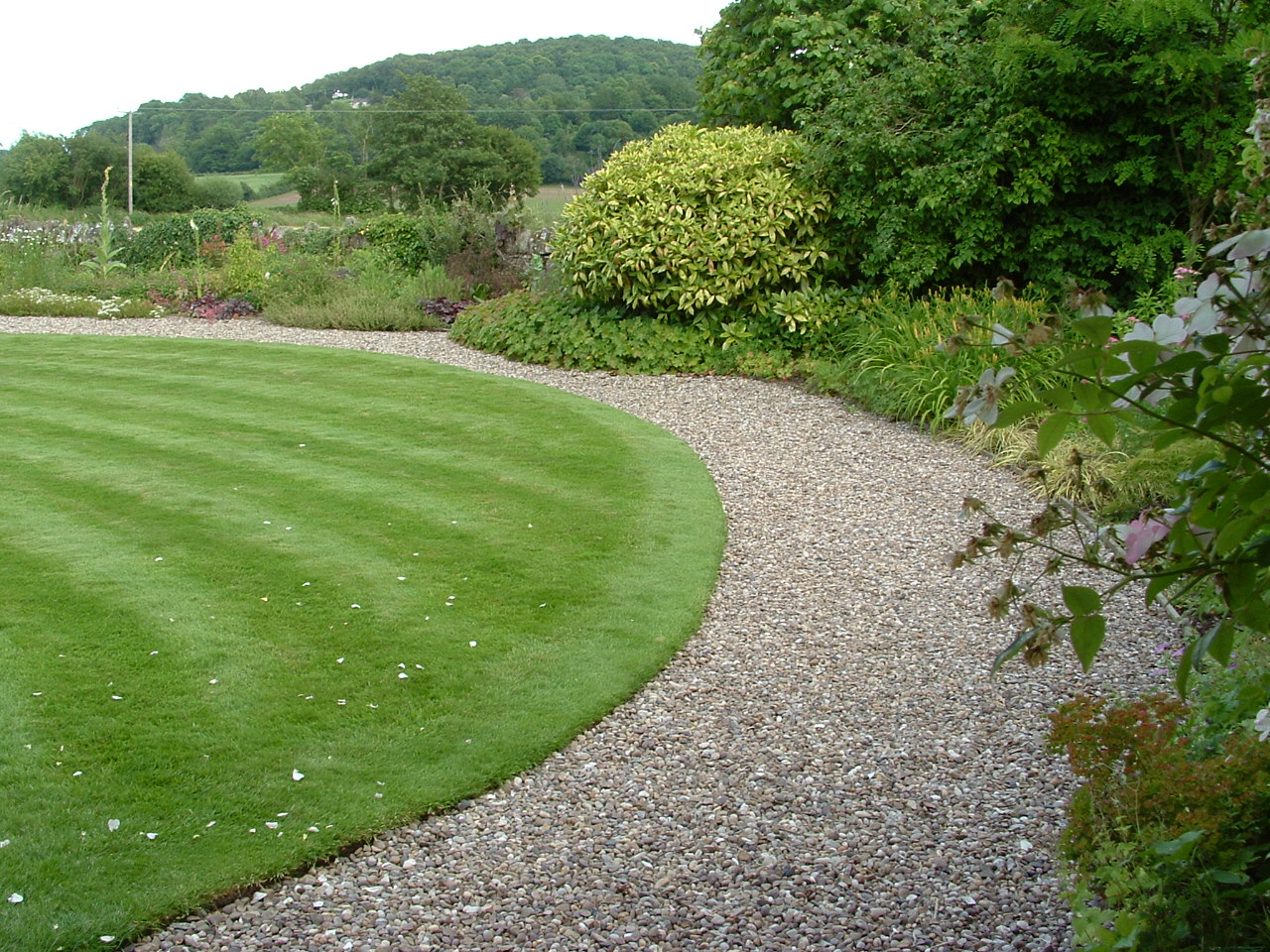 The bold sweep of a gravel path echoes the dramatic sweep of a perfectly mown lawn