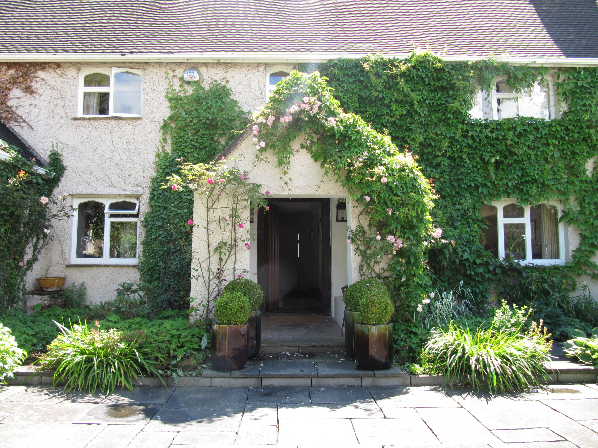 A traditional farmhouse front door, climbing roses give a scented welcome home