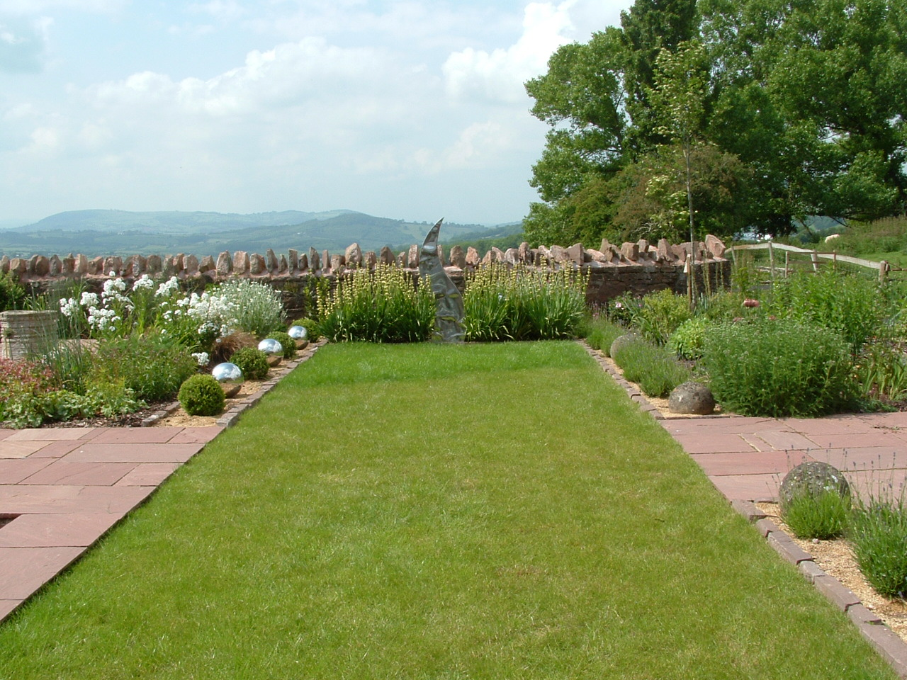 A rectangular lawn with neat paved edges and mixed steel and lavender balls directs the eye directly to the view.