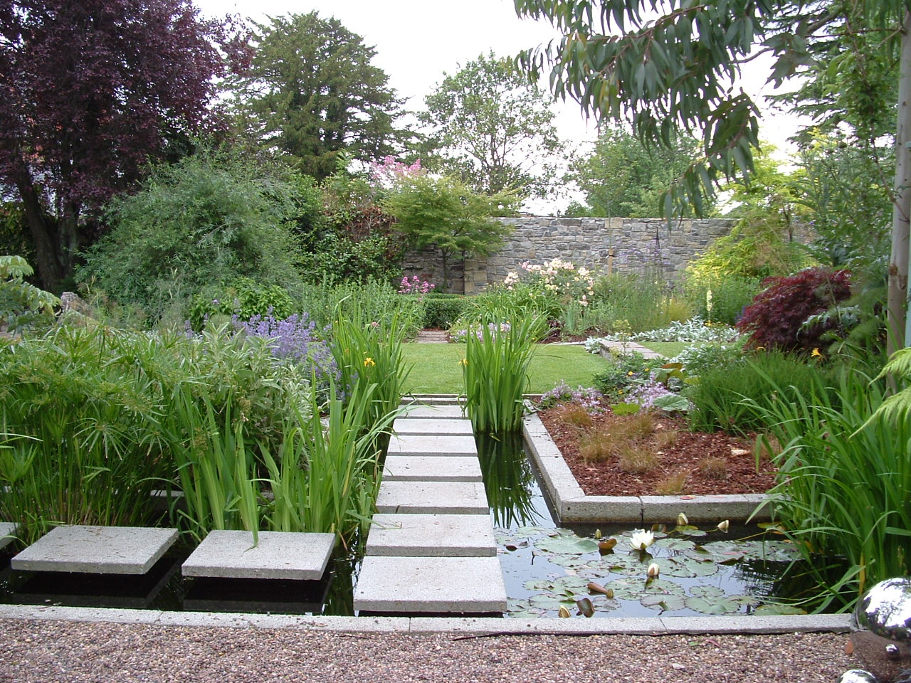 Square stepping stones over a formal pond create a link to another garden room.