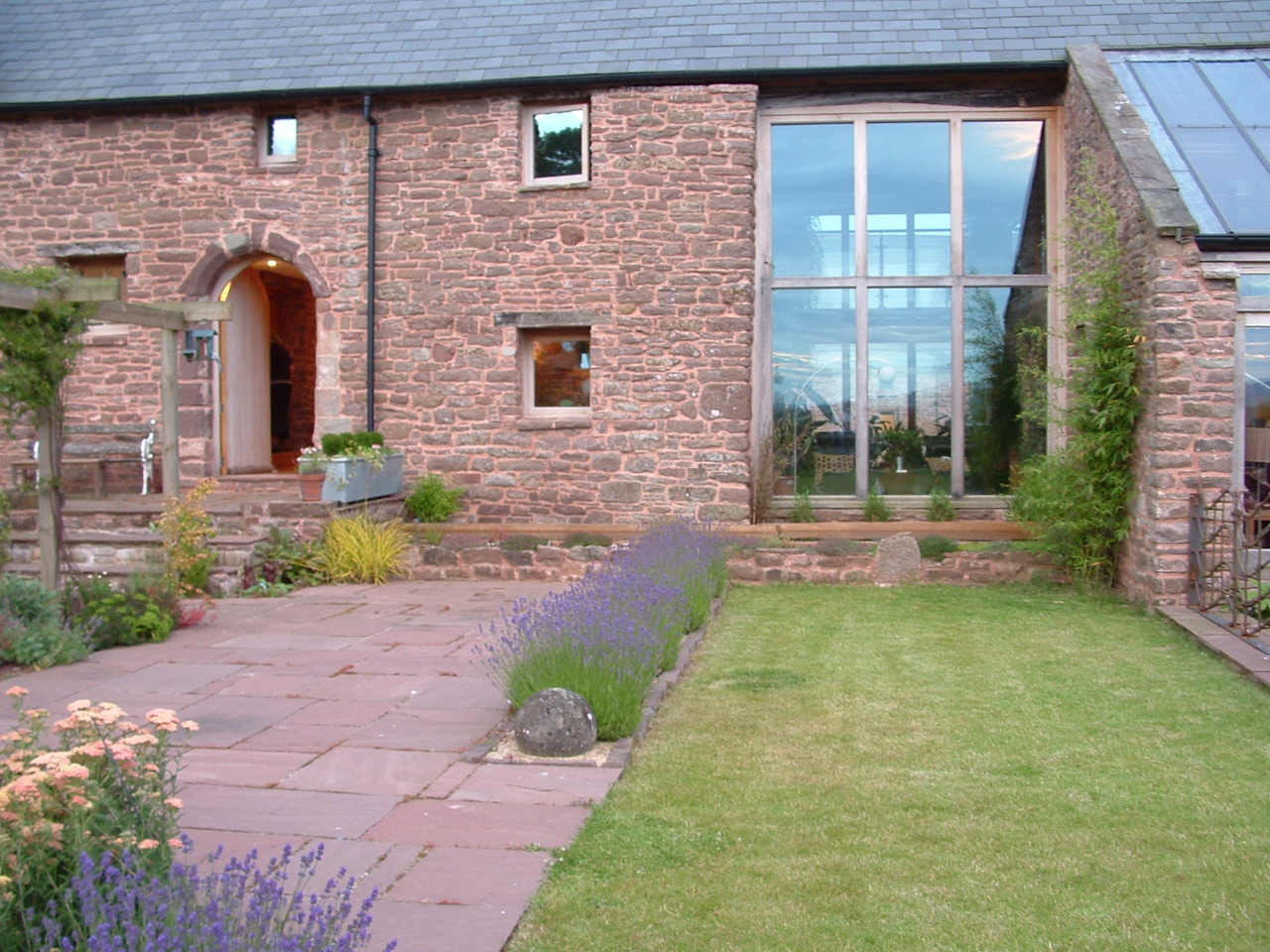 Clipped lavender edges a rectangular lawn outside the large picture windows of a beautiful medieval hall house.