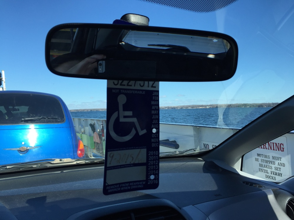 Photo description: View out the front window of a car on a ferry, from inside, showing the car parked in front, the ferry's sides, and a view of the lake and blue sky. In the middle is the rearview mirror with a blue and white accessible parking permit hanging from it