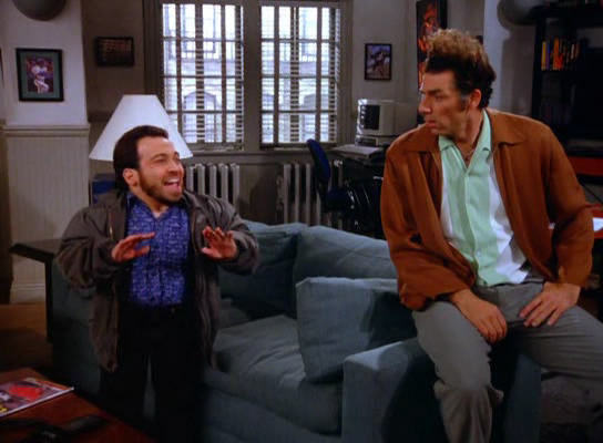 Seinfeld characters Mickey Abbott on the left, Kramer on the right, talking in Jerry's apartment