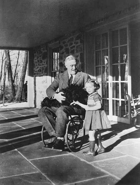 Black and white photo of President Franklin Roosevelt sitting in a wheelchair on a patio, talking to a young girl while holding a small dog in his lap