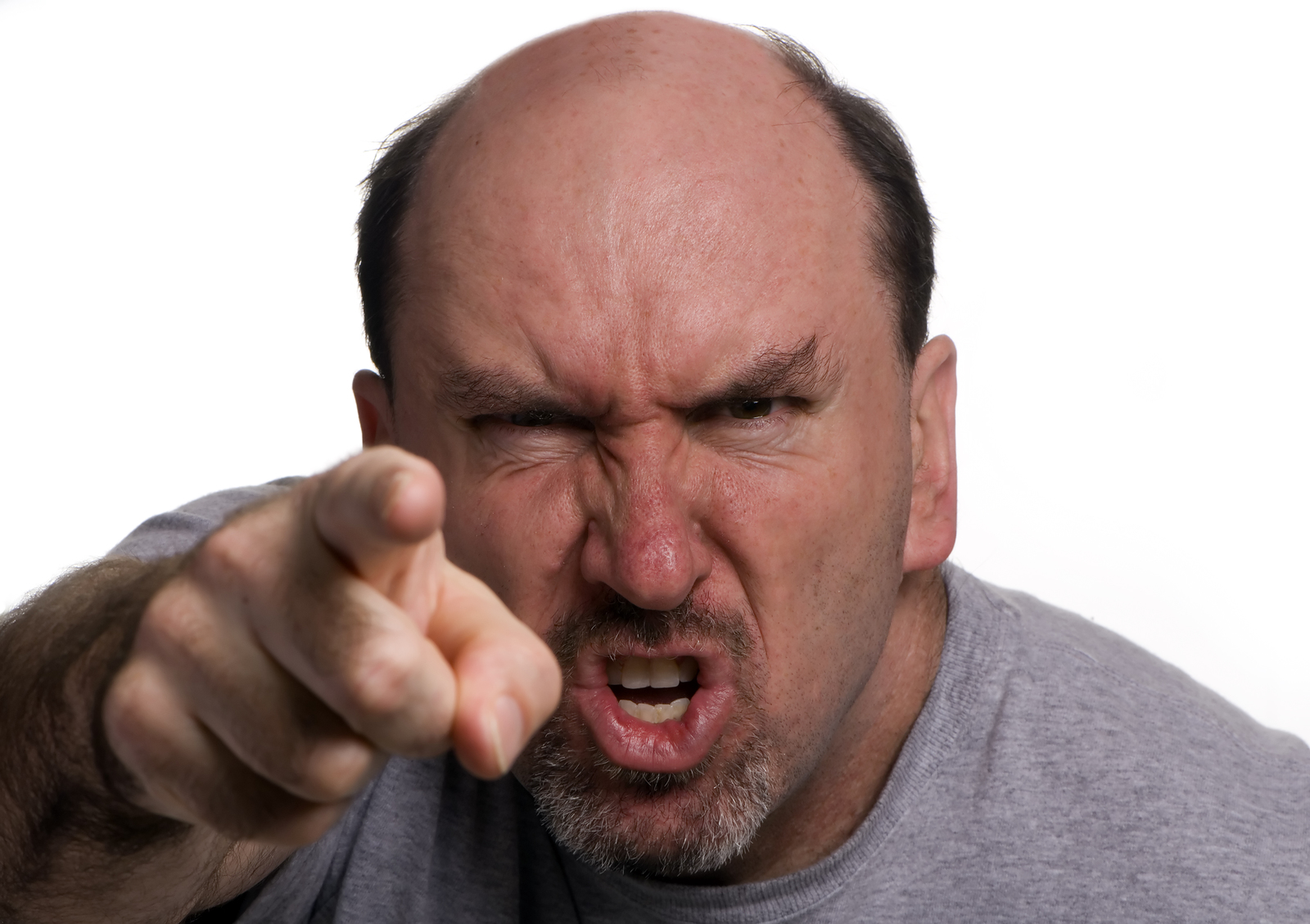 Stock photo of a middle aged white bald man with beard and mustache, looking very angry, pointing an accusing finger at the viewer