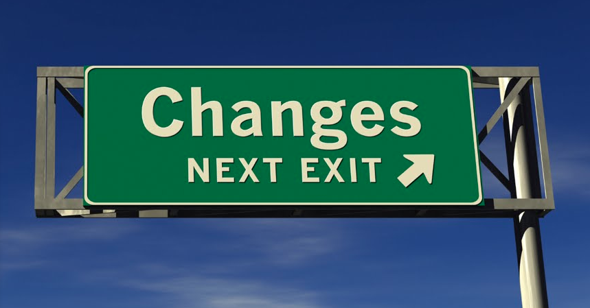 Photo of a green highway sign reading Changes Next Exit against a blue sky background