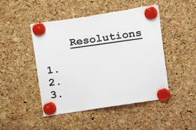 Cork bulletin board with a white rectangular piece of paper pinned to it, reading: Resolutions 1., 2., 3.