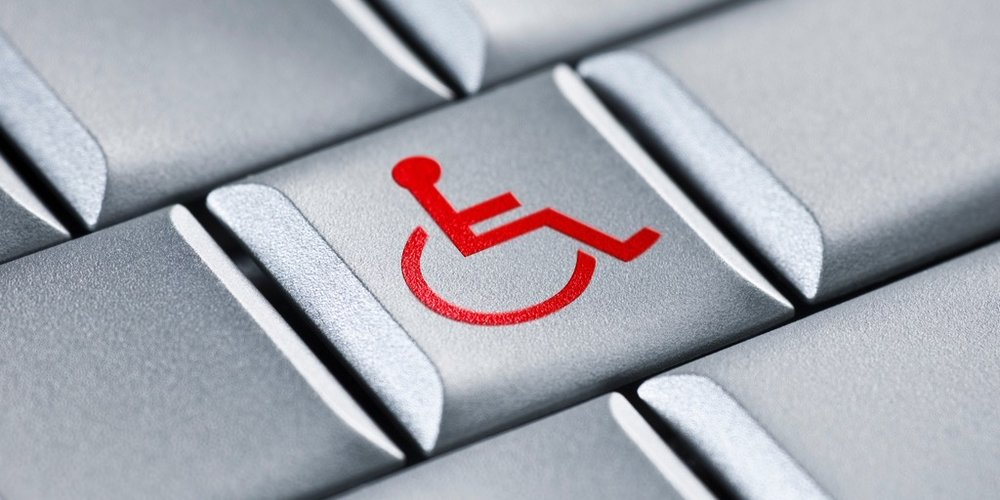 Closeup of a grey computer keyboard, with a red wheelchair symbol on the center key