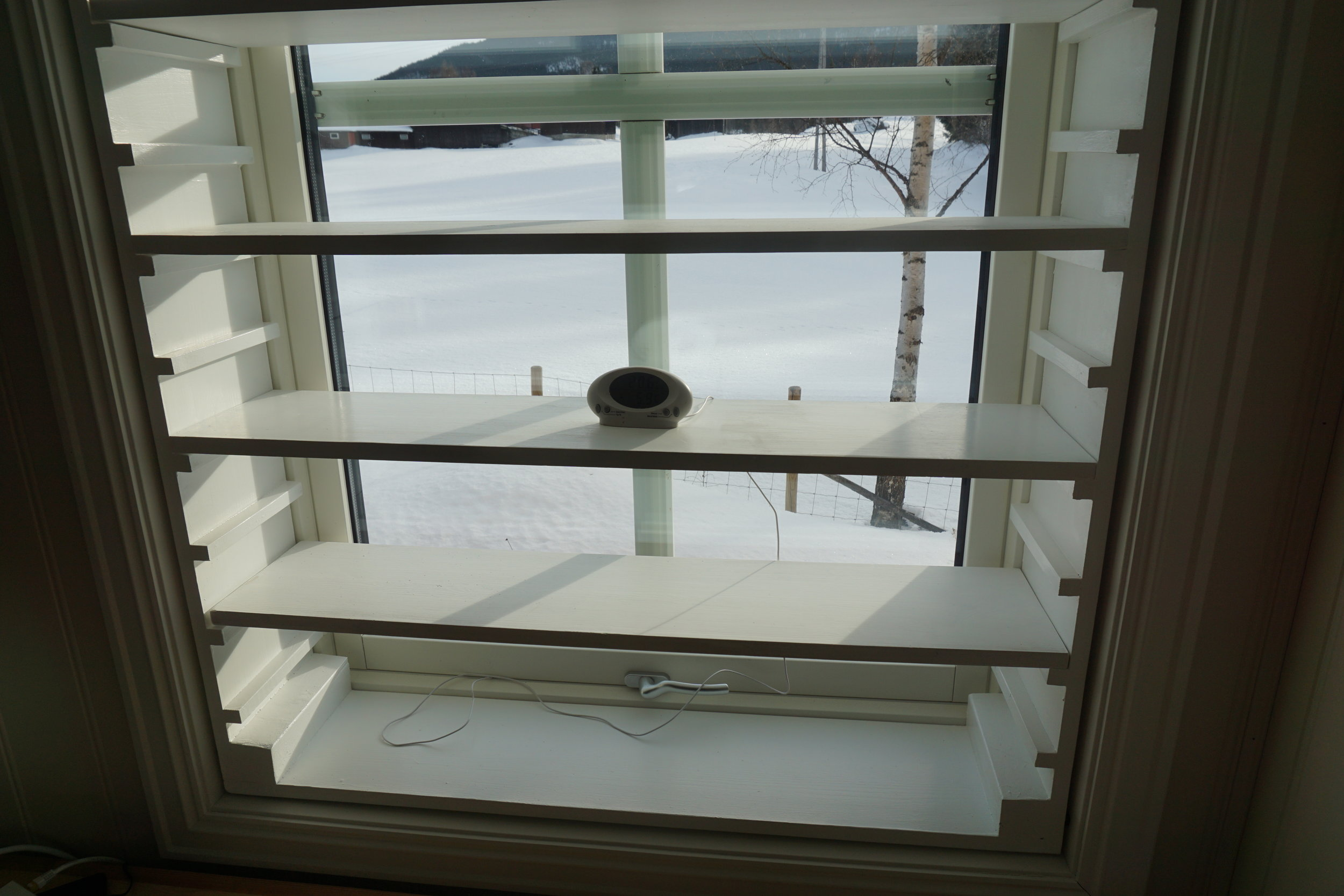 Klar til oppstart. En dyrkingshylle bør være hvit alle veier slik at lyset reflekteres best mulig. Selve konstruksjonen er en hylle som settes løst inn i vinduets lysåpning. Hyllene er løse og justeres etter behov. Det er viktig å følge med på temperaturene.