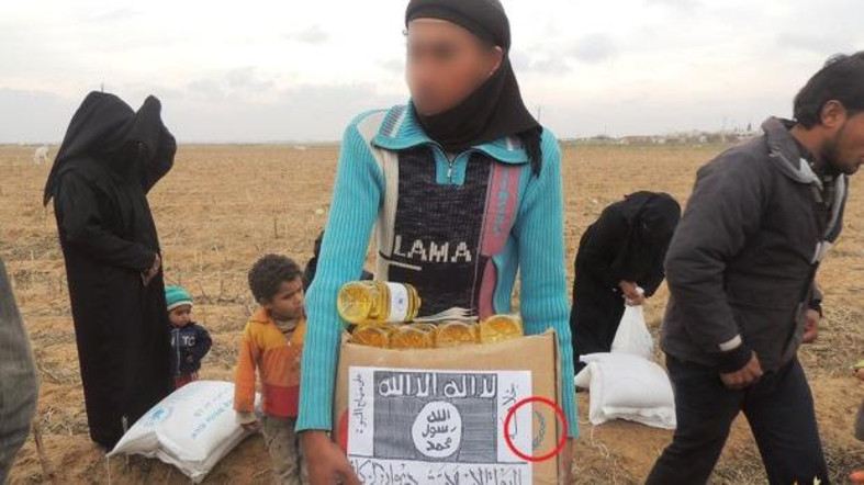 Boxes of aid with the WFP logo covered by IS signs
