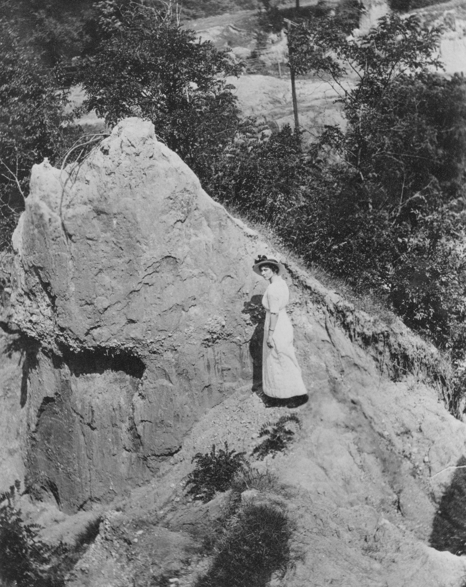A woman stands in Tapps' Hole, the location that Raleigh settler William Tapp used as shelter and a base for hunting and exploring.
