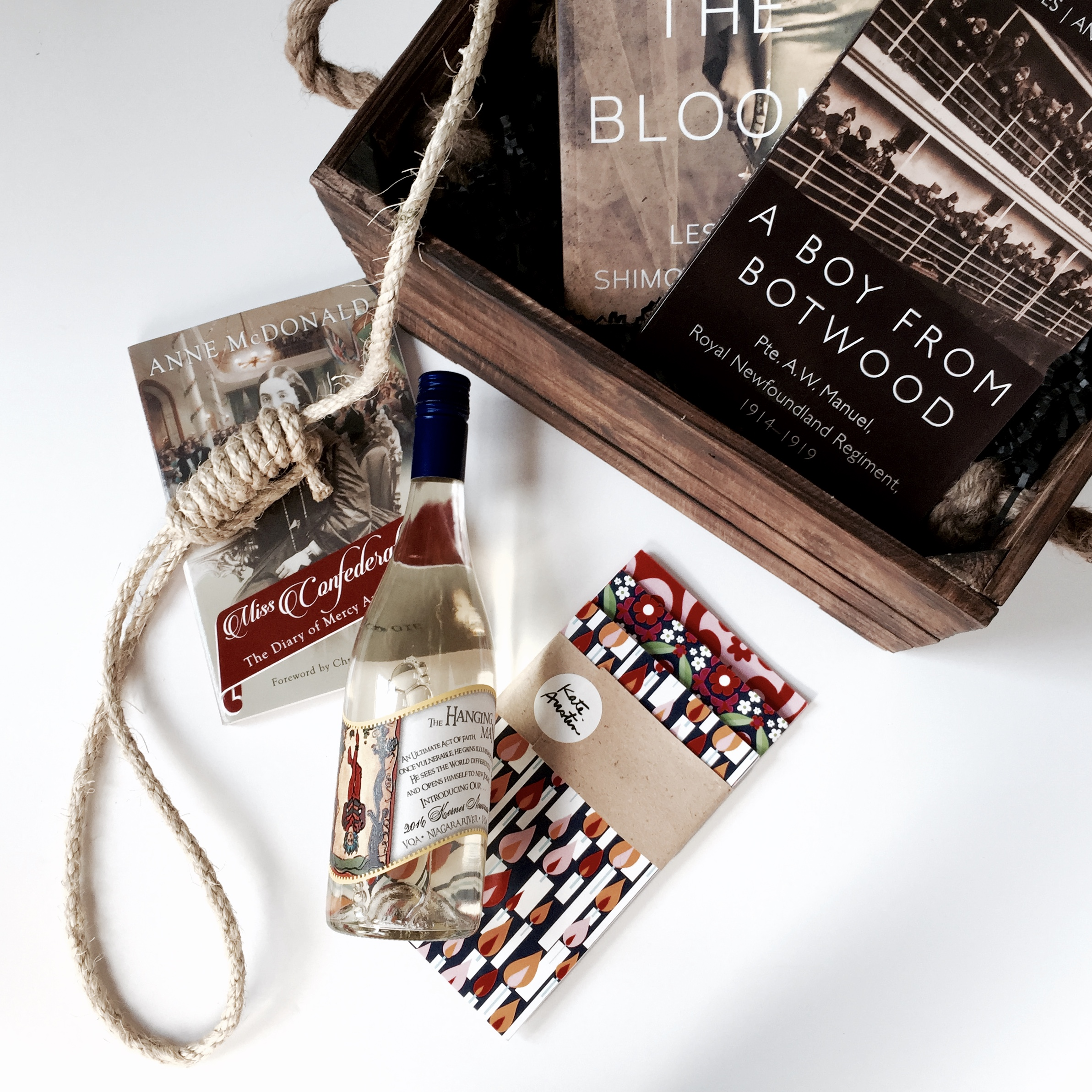 """The gift basket contained three notebooks with covers designed by local Toronto artist  Kate Austin ; a bottle of wine, """"The Hanging Man""""; and three books,  After the Bloom  by Leslie Shimotakahara,  A Boy from Botwood  by Brian Davies and Andrew Traficante, and Miss Confederation by Anne McDonald."""