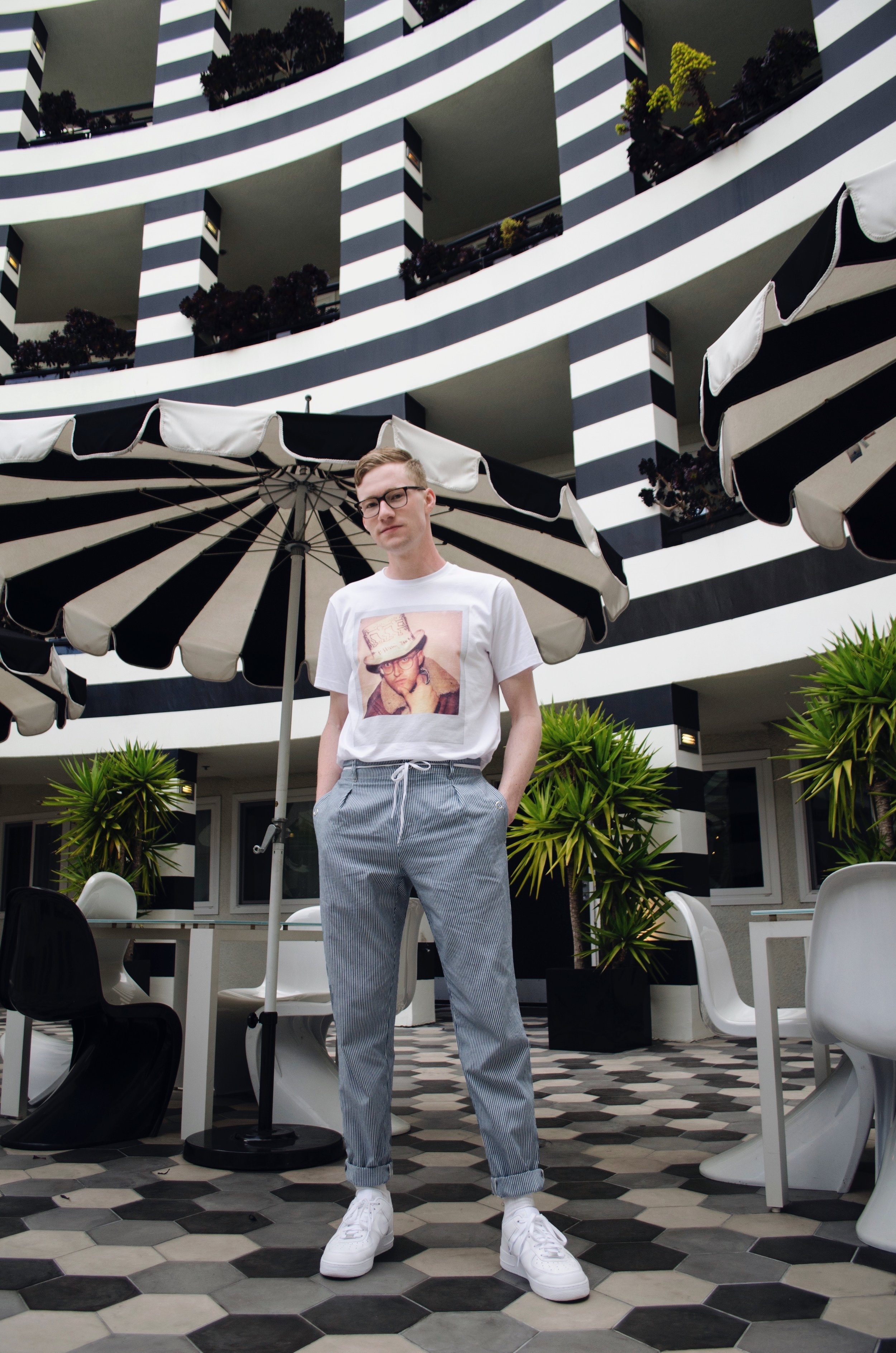Wearing Coach  T-shirt , A.P.C.  trousers , Nike Air Force  sneakers ,Warby Parker  glasses