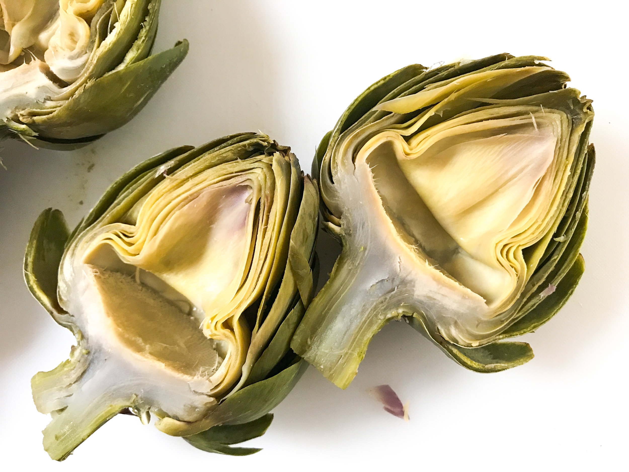 The boiled artichoke halves, after the fuzzy chokes and spiky inner leaves have been scooped out.
