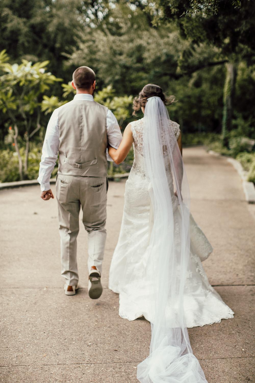 Wedding couple walking through Zilker Botanical Gardens after exchanging vows in Austin, Texas.