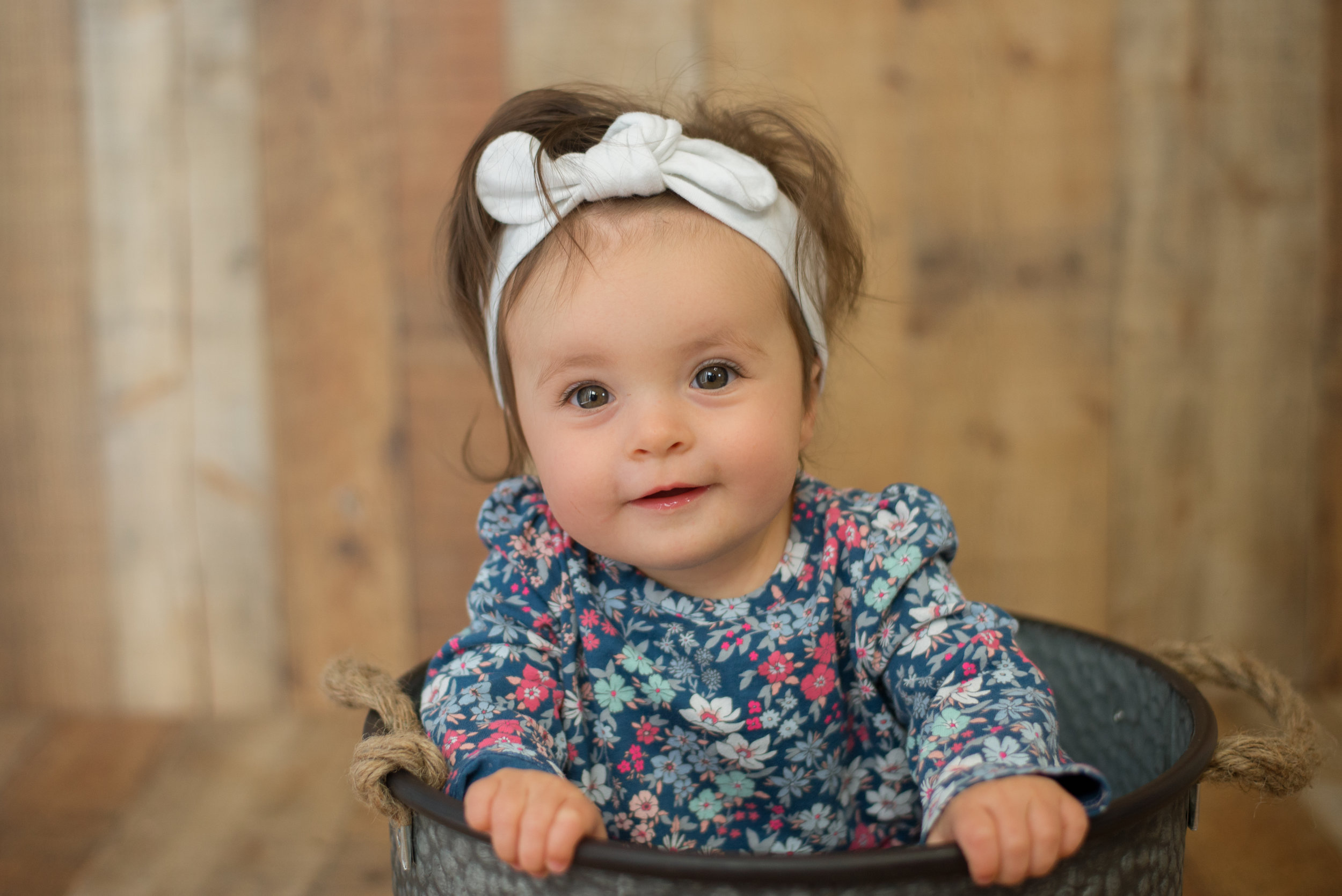 baby girl with lots of hair smiles at camera during wilmington nc photography session