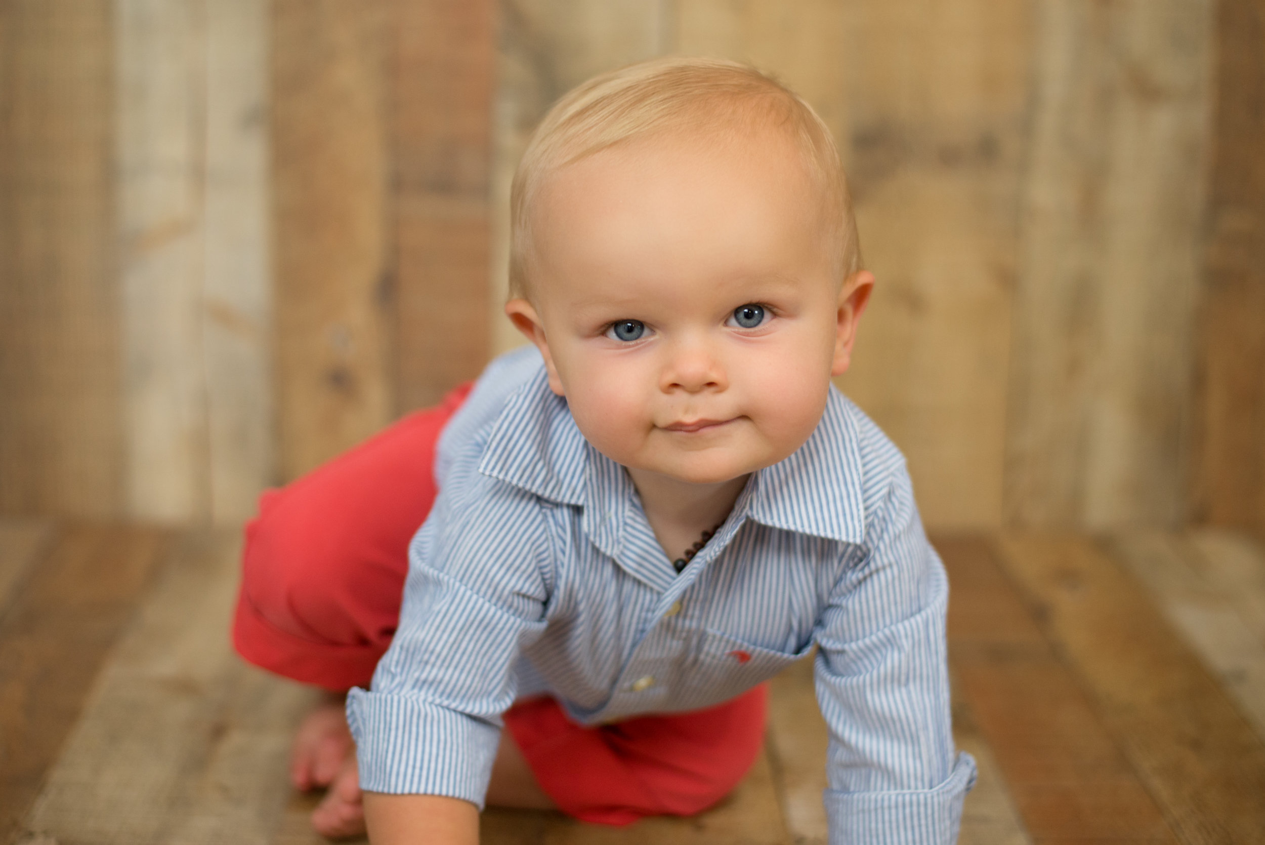 baby boy with blue eyes crawls towards camera