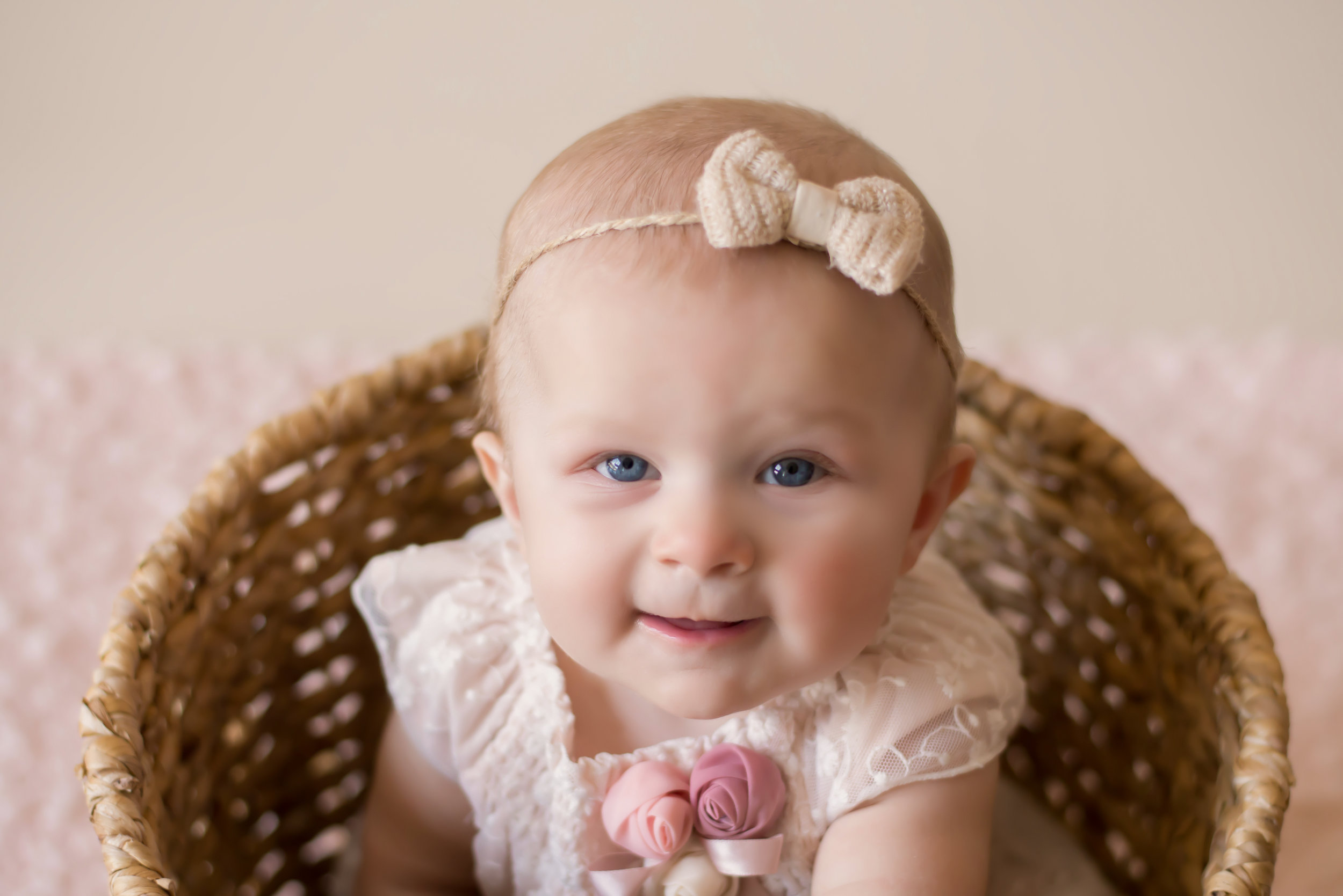 baby girl with blue eyes sits in basket during Wilmington nc baby photography session