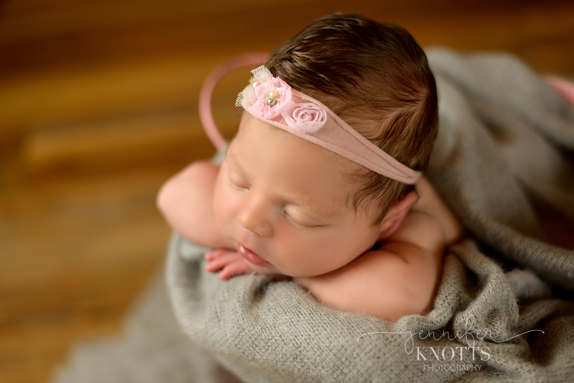 baby girl rests in bucket surrounded by gray fabric during Wilmington newborn session
