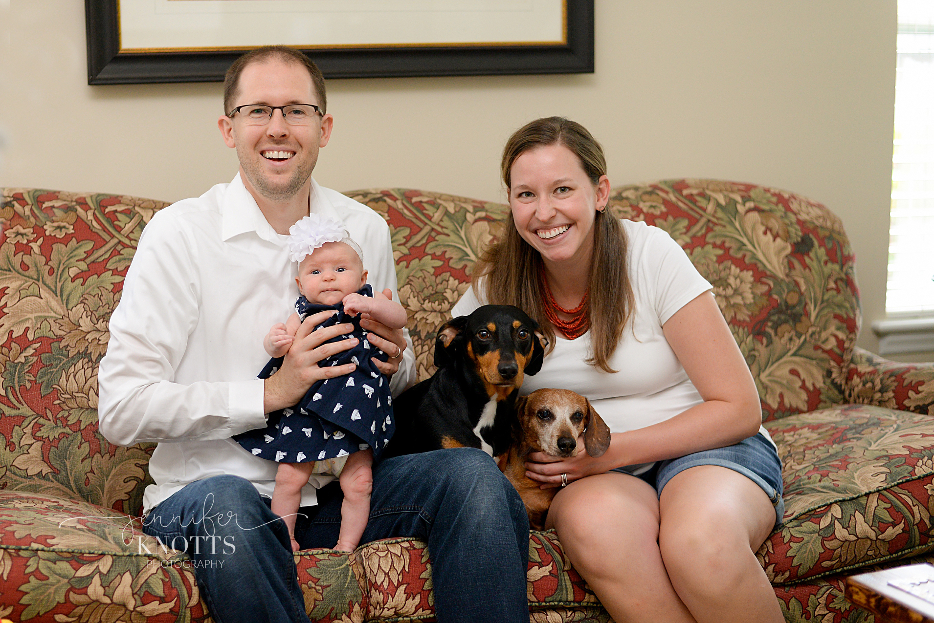 parents pose for photo with newborn daughter and two dogs on couch