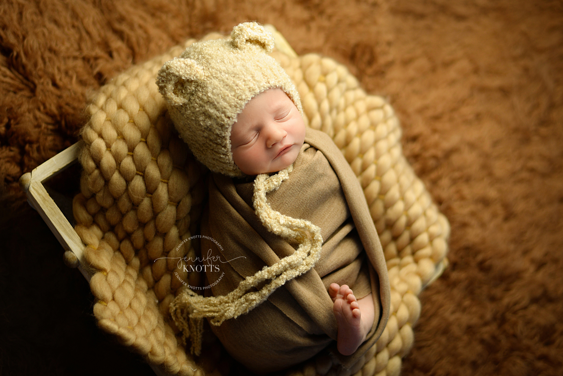 newborn photographer captures baby boy sleeping with bear bonnet
