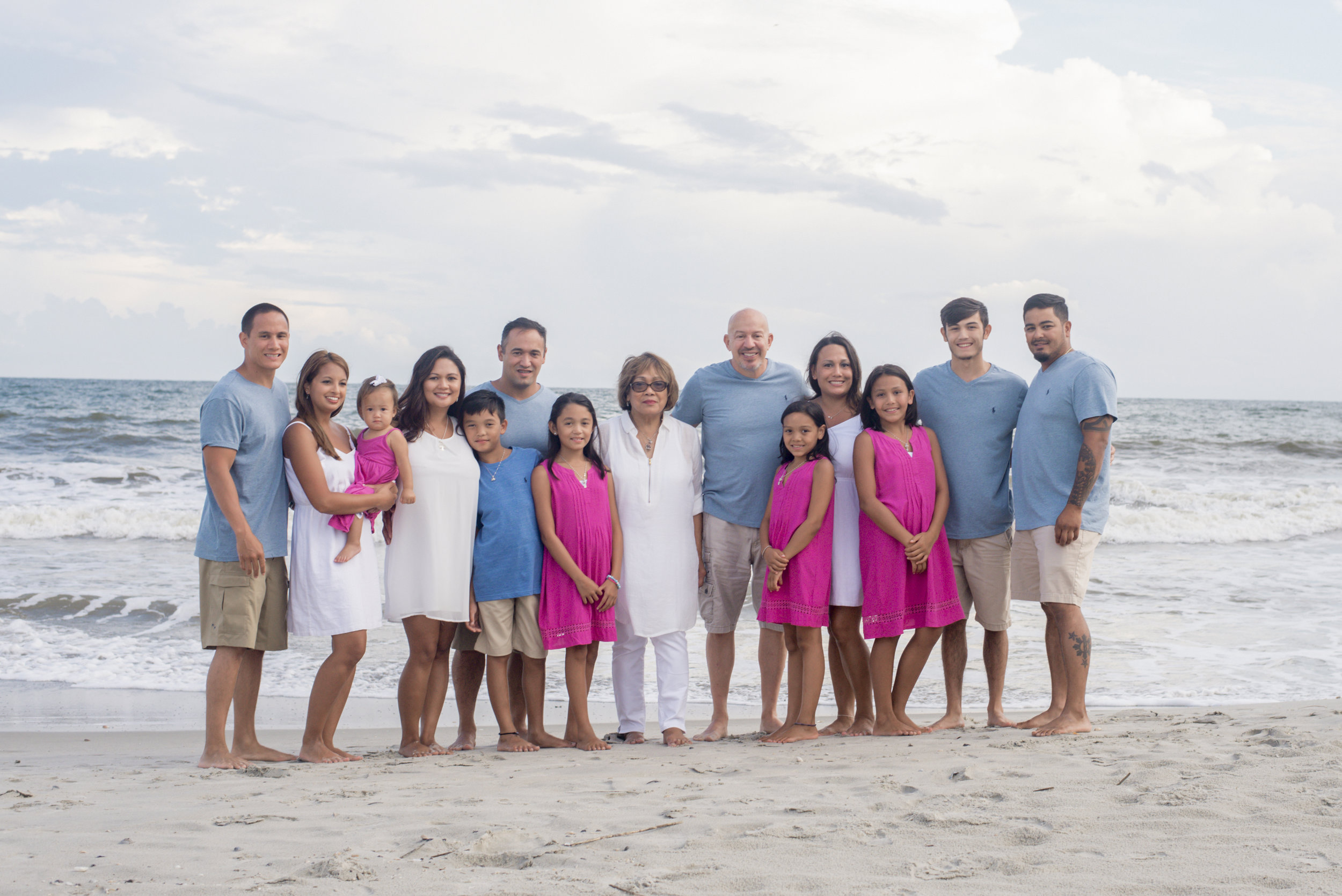 holden beach photographer poses extended family in front of ocean