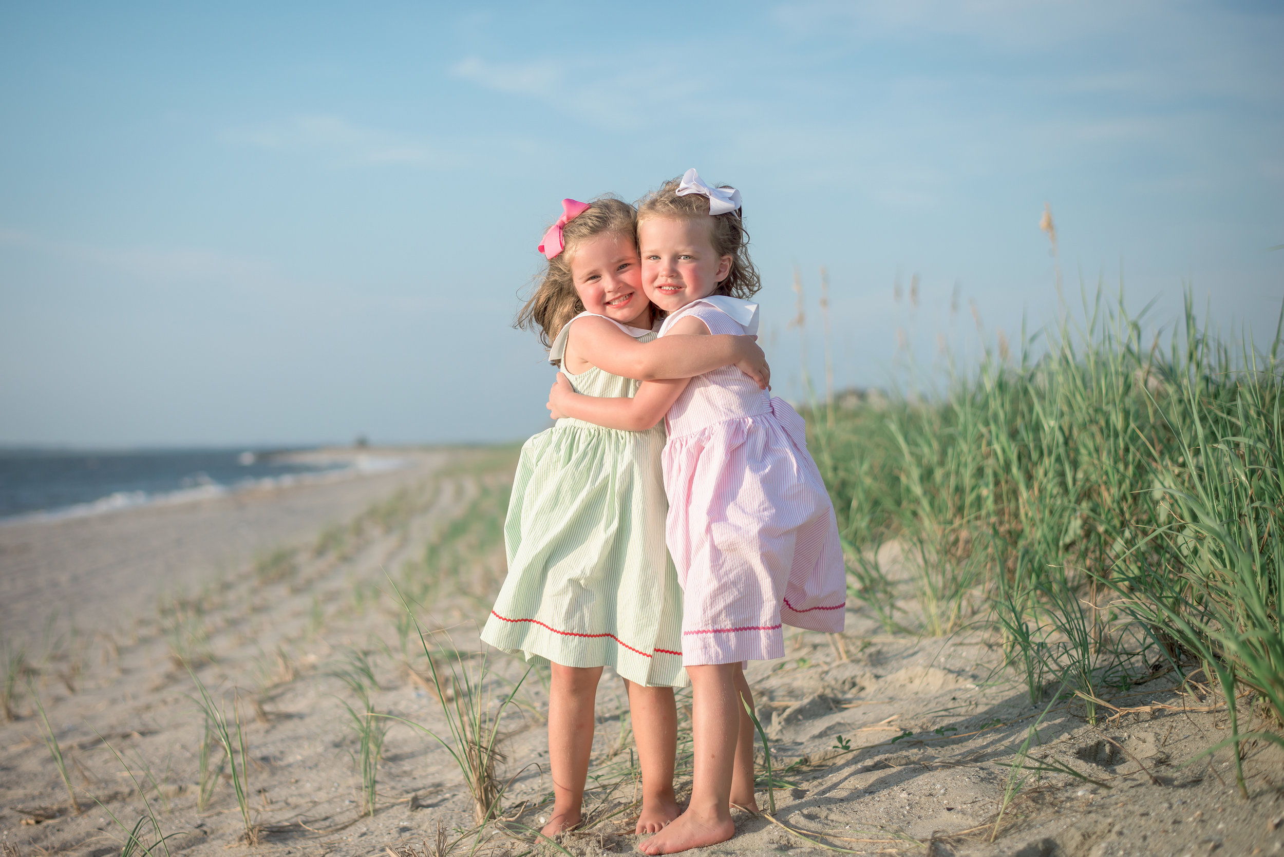 bald head island photographer captures two little girls hugging on shore