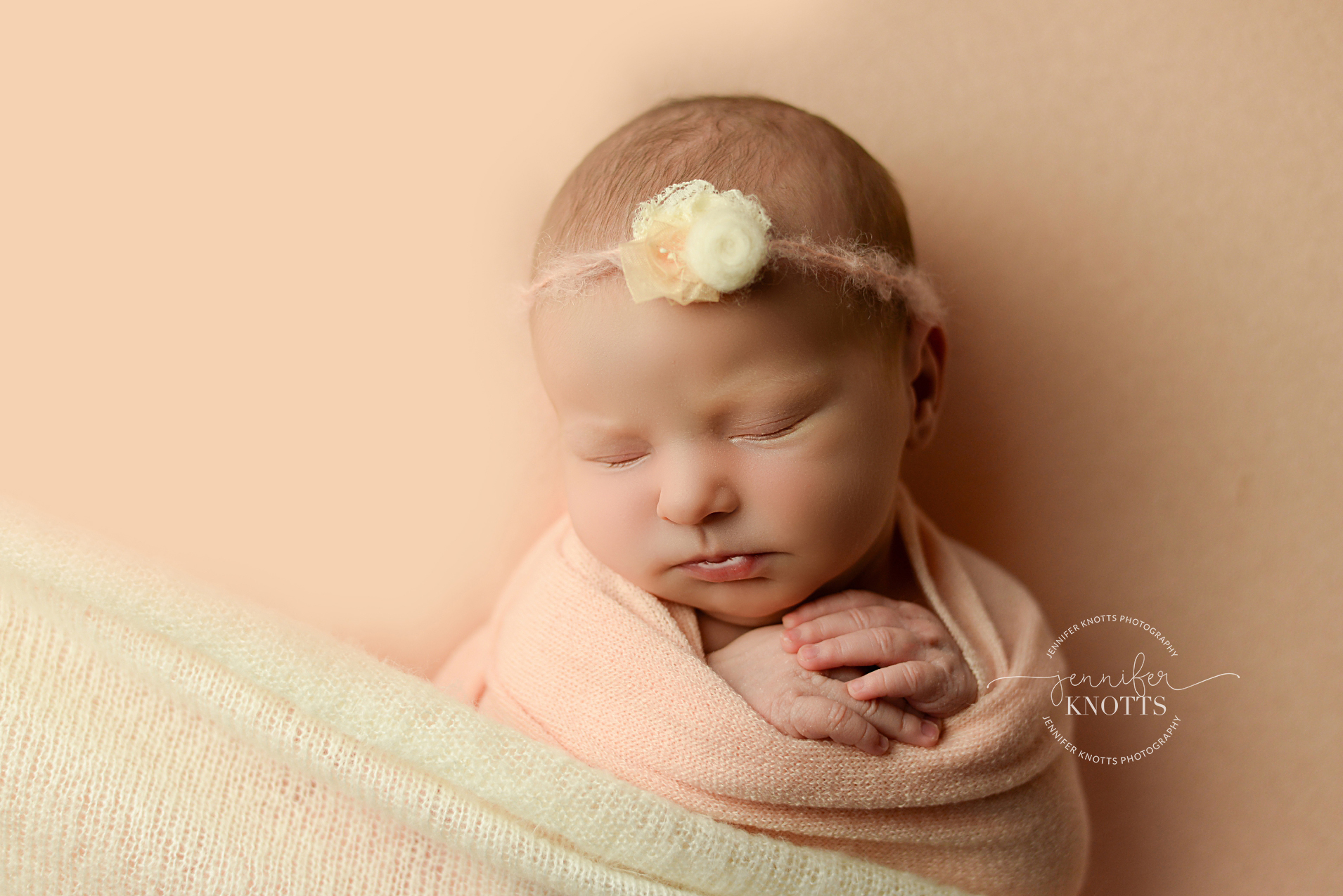 Wilmington newborn photographer captures baby girl wrapped in peach fabric
