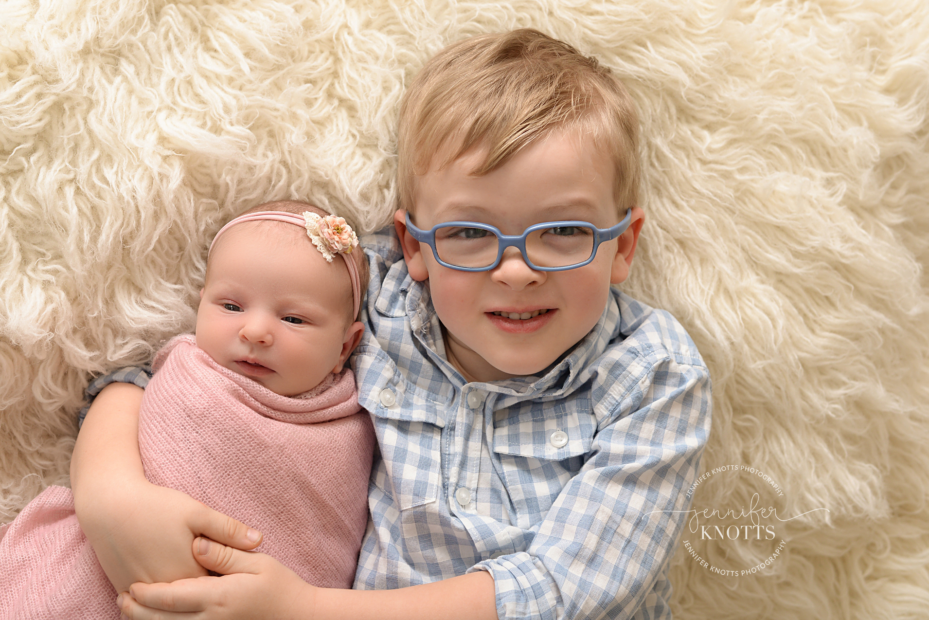 toddler boy cuddles baby sister on cream background during Wilmington newborn session