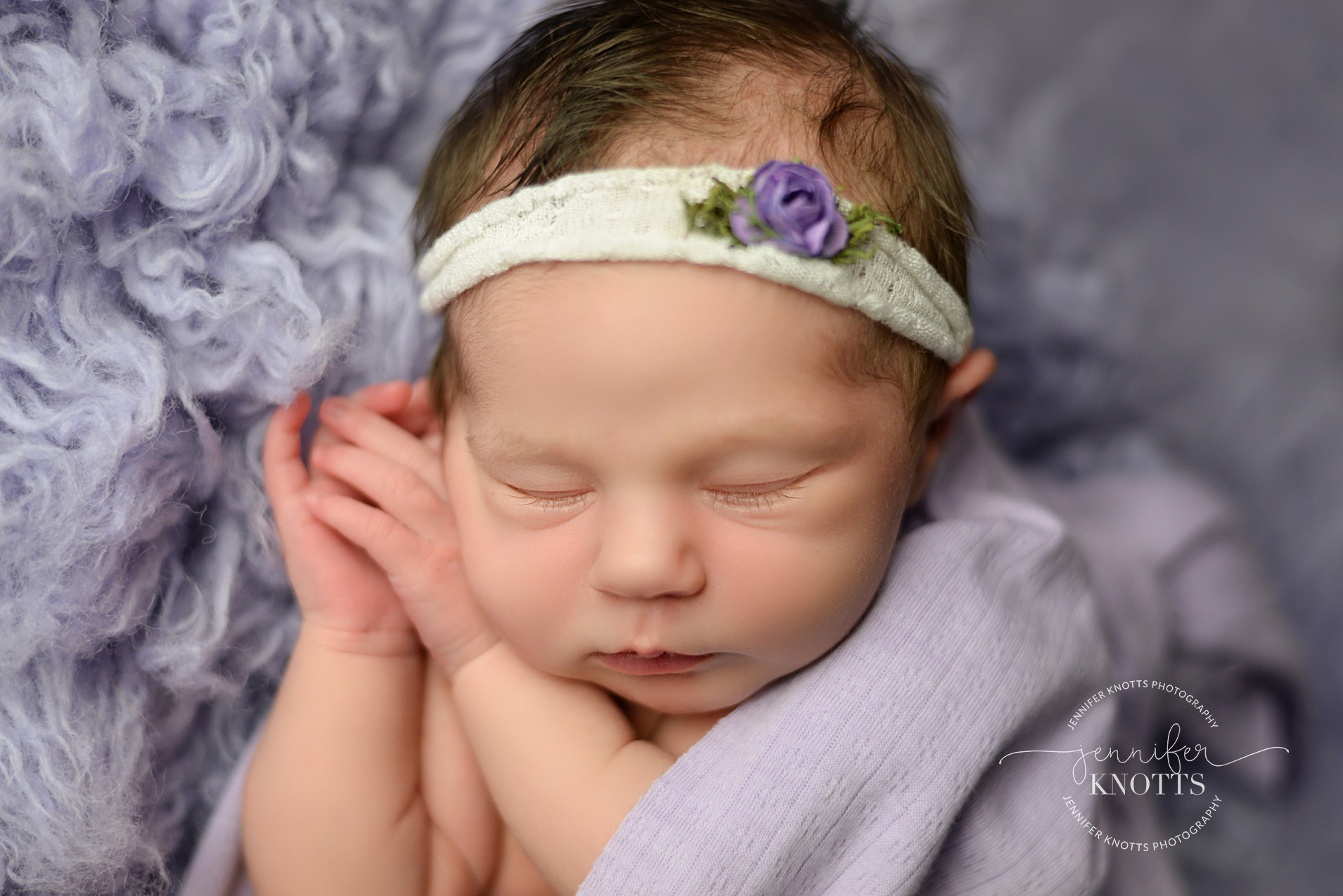 Newborn girl sleeps with hands under face wrapped in purple
