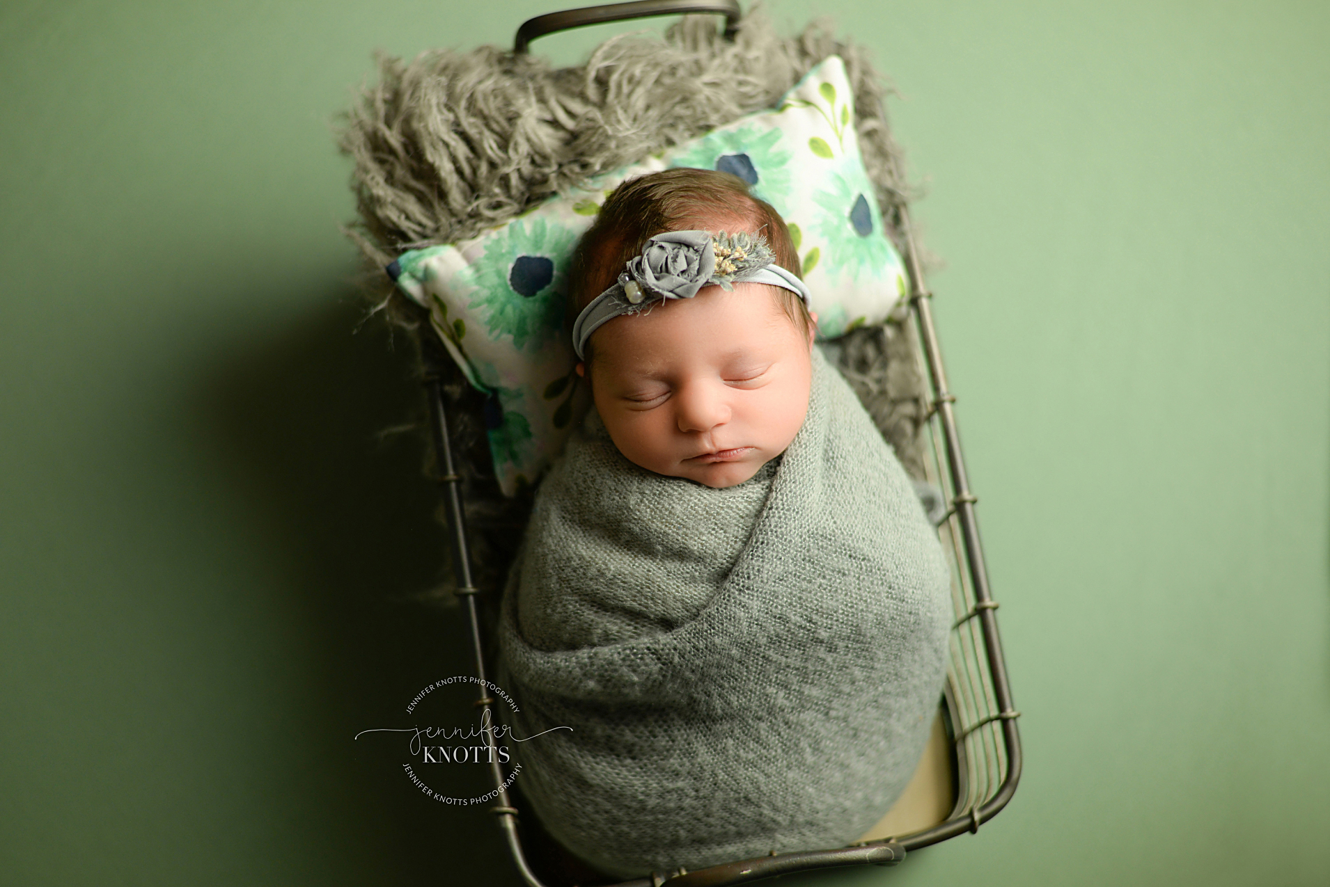 baby girl sleeps in basket on green backdrop during Wilmington nc newborn session