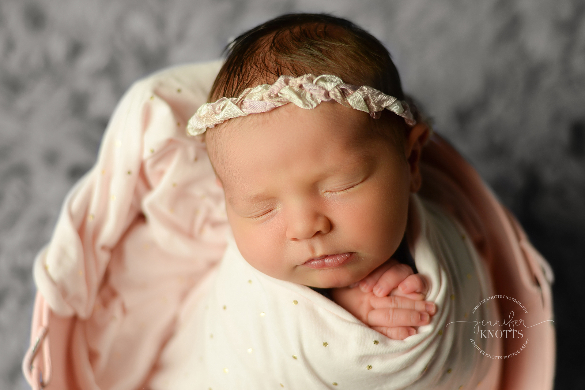 newborn girl wrapped in polka dot fabric poses in pink bucket