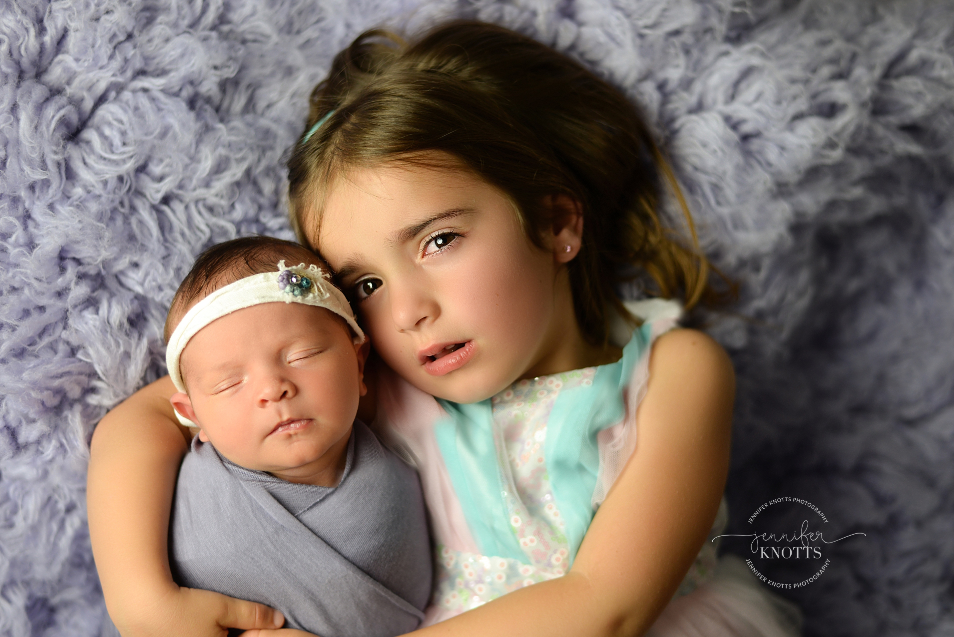 big sister cuddles newborn wrapped in purple during wilmington newborn session