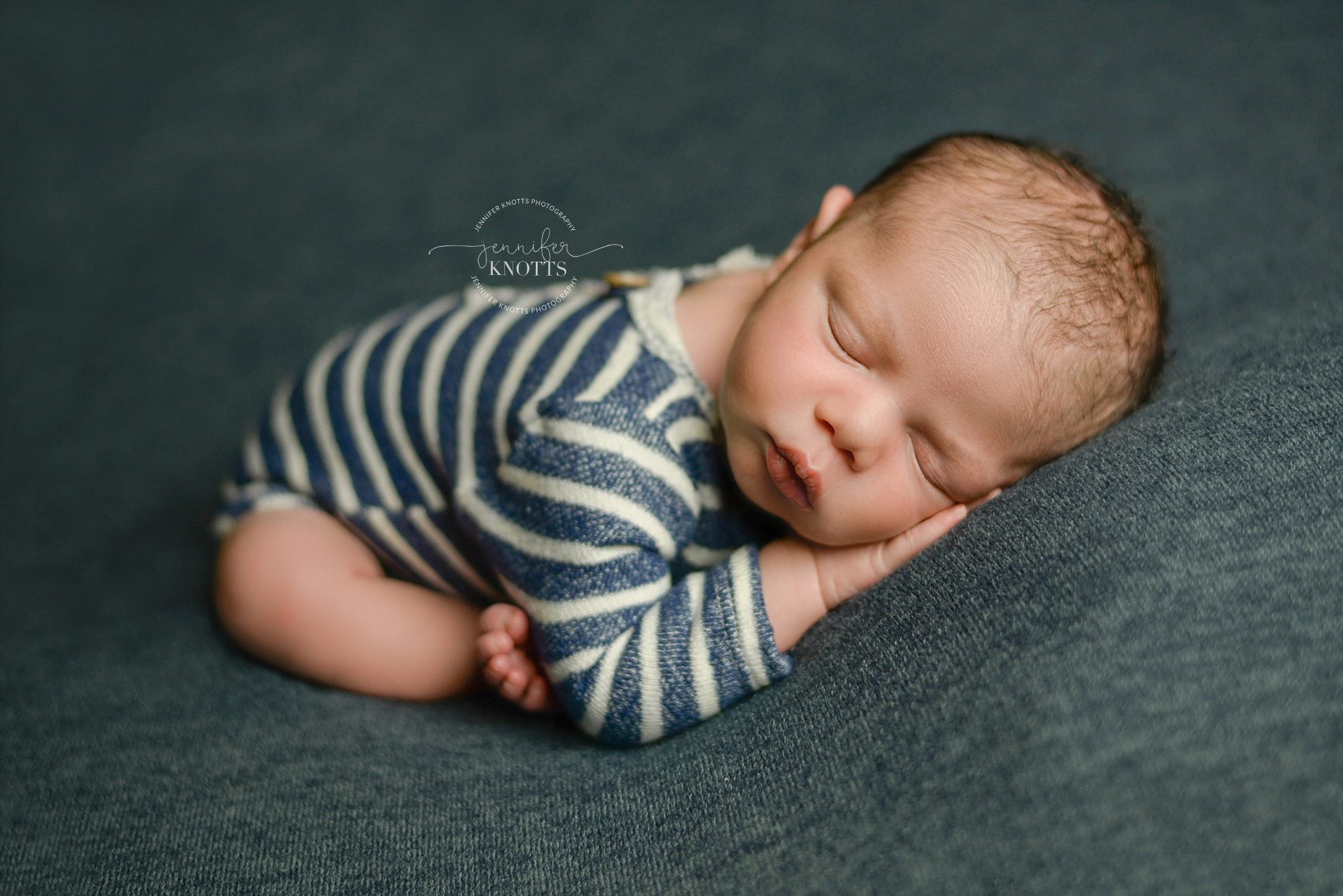 newborn boy sleeps on blue fabric while wearing striped blue outfit