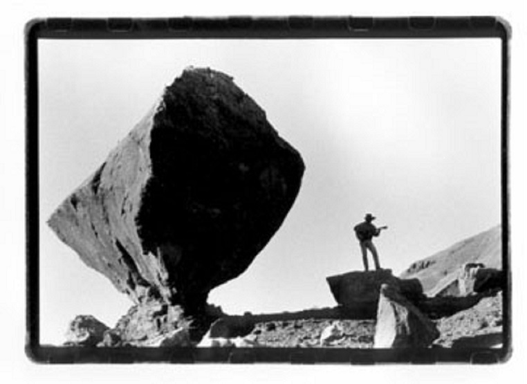 Peter McLaughlin at Vemilion Cliffs National Monument with guitar and balanced rock.JPG