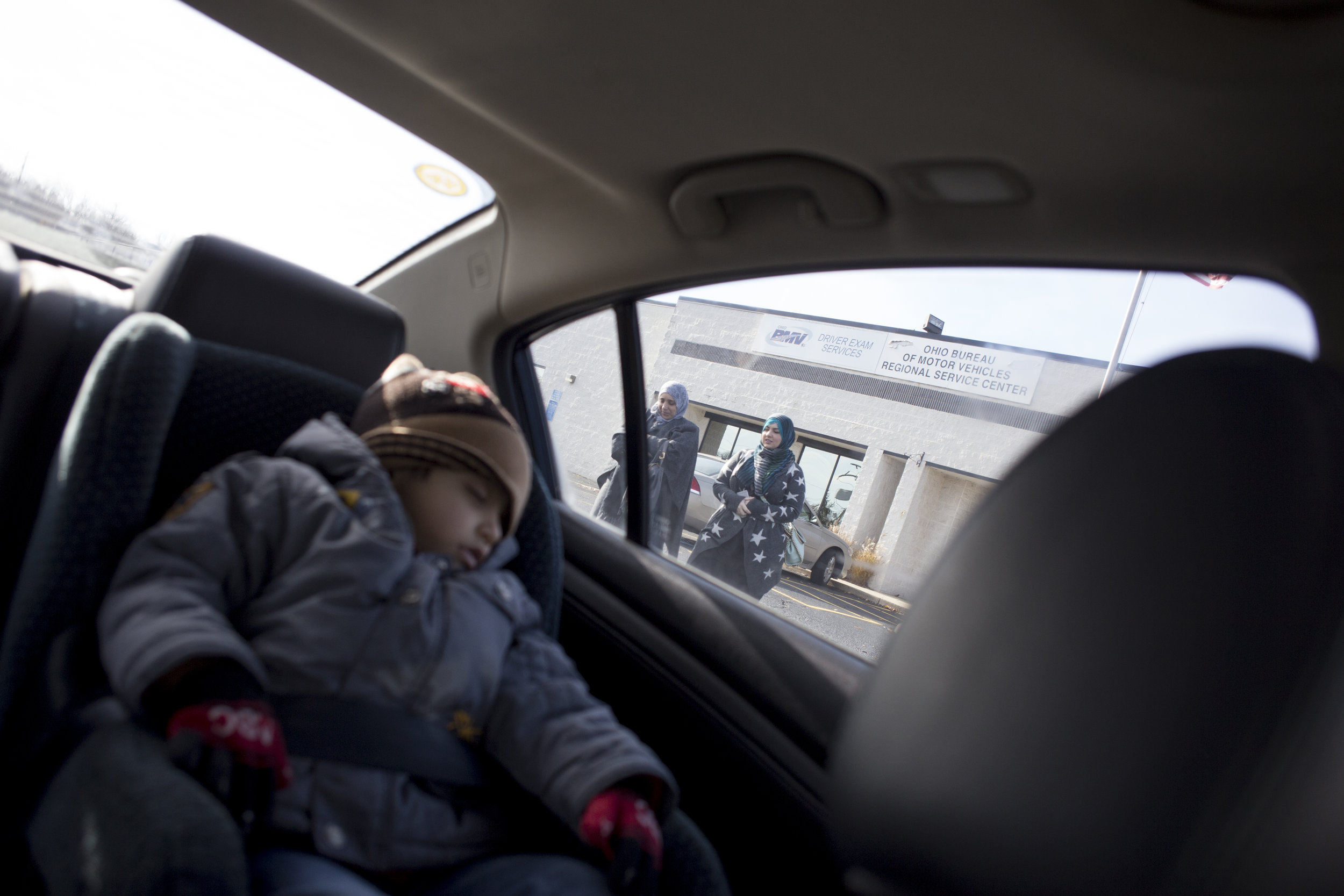 Two year-old Mohamad sleeps in the car as his mother Mariam and Runah, a volunteer for Salaam Cleveland, leave the Bureau of Motor Vehicles after Mariam received news that she failed her drivers permit exam on Wednesday, Dec. 7, 2016.