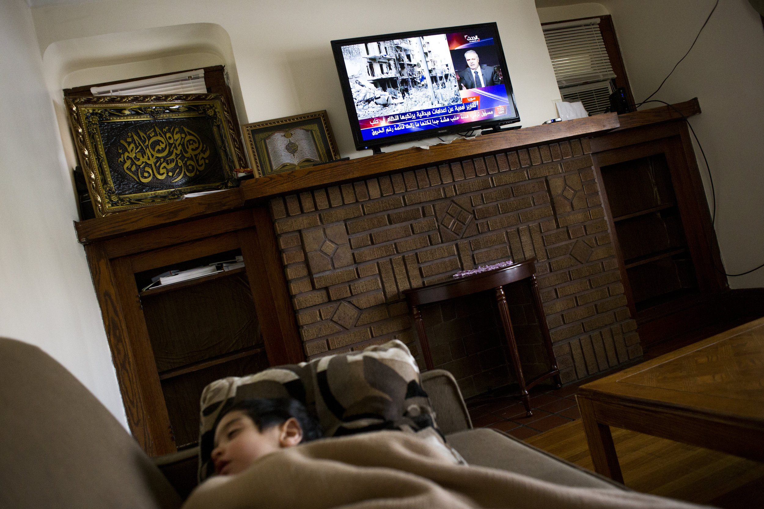 News on the conflict in Syria is broadcast on the television while Mohamad sleeps in his home.