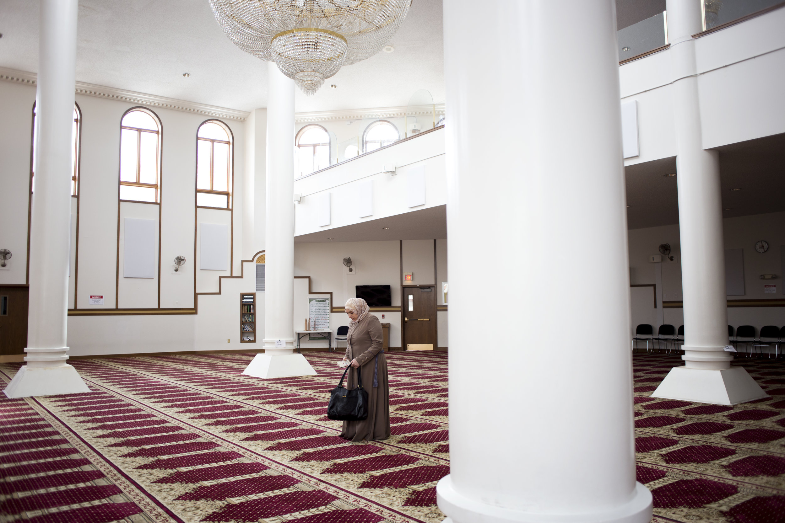 """Mariam visits the Islamic Center of Cleveland for the first time since she arrived in the States on Monday, Dec. 5, 2016. As she stepped into the prayer room, she stopped at a white pillar and looked up into the light for a moment. """"I'm really happy to see a mosque like this because in these four to five months, I haven't seen a mosque this beautiful,"""" Mariam said."""